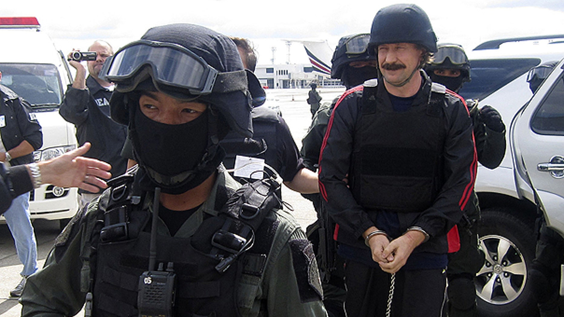 FILE: Russian arms trafficker Viktor Bout, right, escorted by Thai police commandos, arrives at Don muang airport in Bangkok .