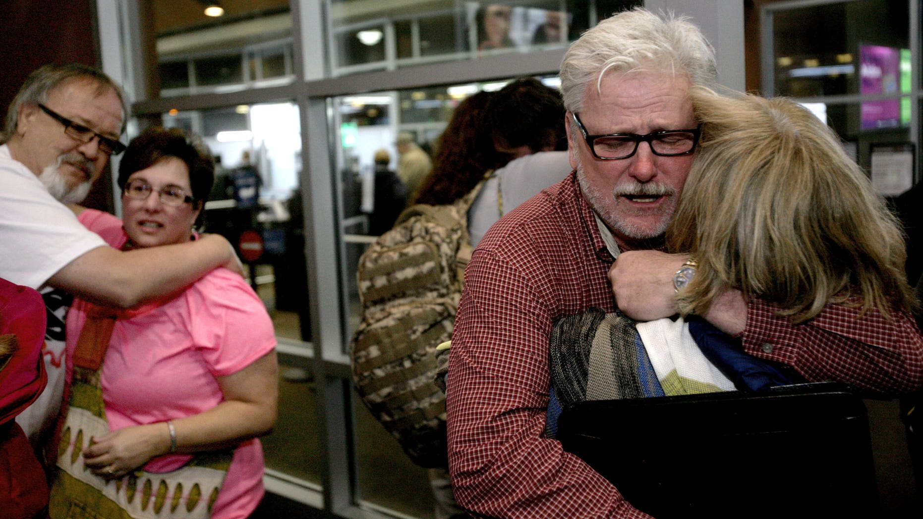Freed aid workers Arlynn Hefta, right, and Kermit Paulson, left, embrace their wives at Hector International Airport, Tuesday, March 3, 2015 in Fargo, N.D.
