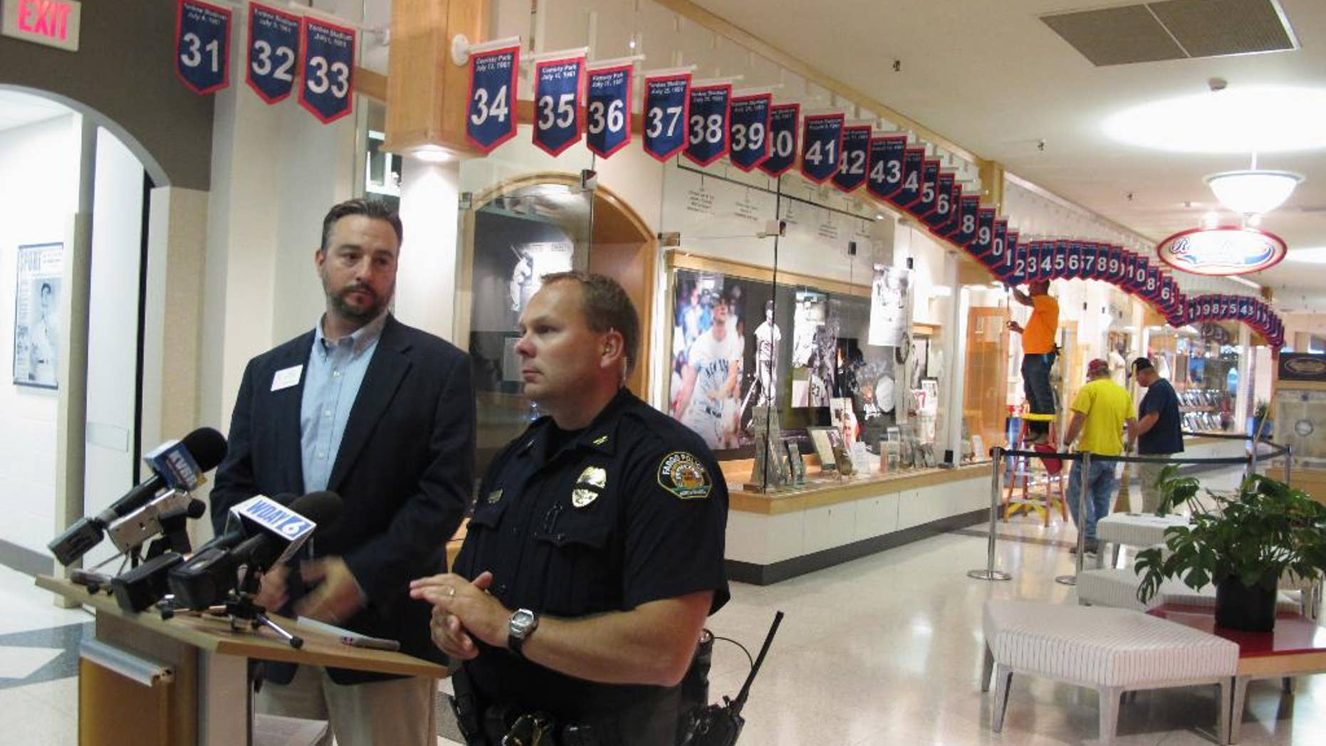 West Acres Mall property manager Chris Heaton, left, and Fargo Deputy Police Chief Joe Anderson talk in front of the Roger Maris Museum in Fargo, N.D., on Tuesday, July 26, 2016, while workers repair a display where an ornate belt was stolen from the mall early Tuesday. Maris, who grew up in Fargo, won the Hickok Belt in 1961 when he hit 61 home runs, a record at the time. The award has gone to the top professional athletes in the country. (AP Photo/Dave Kolpack)