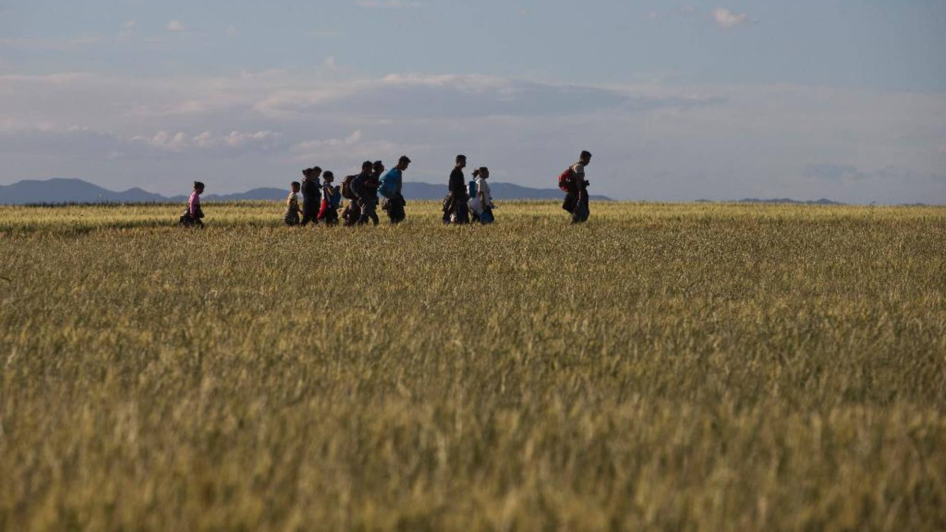 Migrants and refugees walk among fields on their way to Idomeni camp, after trying to cross the Greek-Macedonian border, Saturday, May 14, 2016. Thousands of stranded refugees and migrants are camped at the makeshift refugee camp of the northern Greek border point of Idomeni. (AP Photo/Petros Giannakouris)