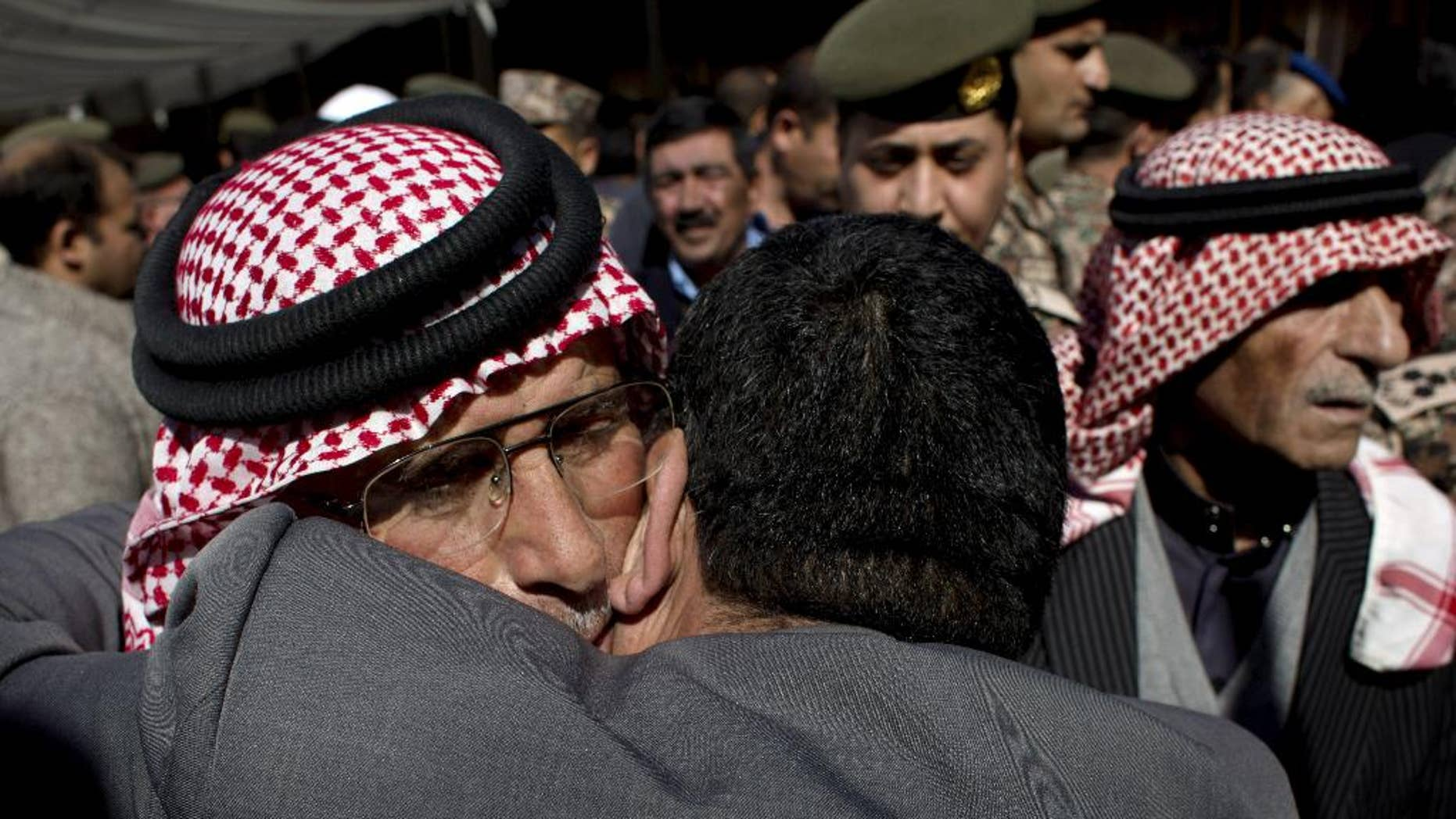 Safi al-Kaseasbeh, left, father of slain Jordanian pilot, Lt. Muath al-Kaseasbeh receives condolences at the Kaseasbeh tribe's gathering divan at their home village of Ai, near Karak, Jordan, Wednesday, Feb. 4, 2015. Outrage and condemnation poured across the Middle East on Wednesday as horrified people learned of the video purportedly showing the Islamic State group burn a Jordanian pilot to death. (AP Photo/Nasser Nasser)