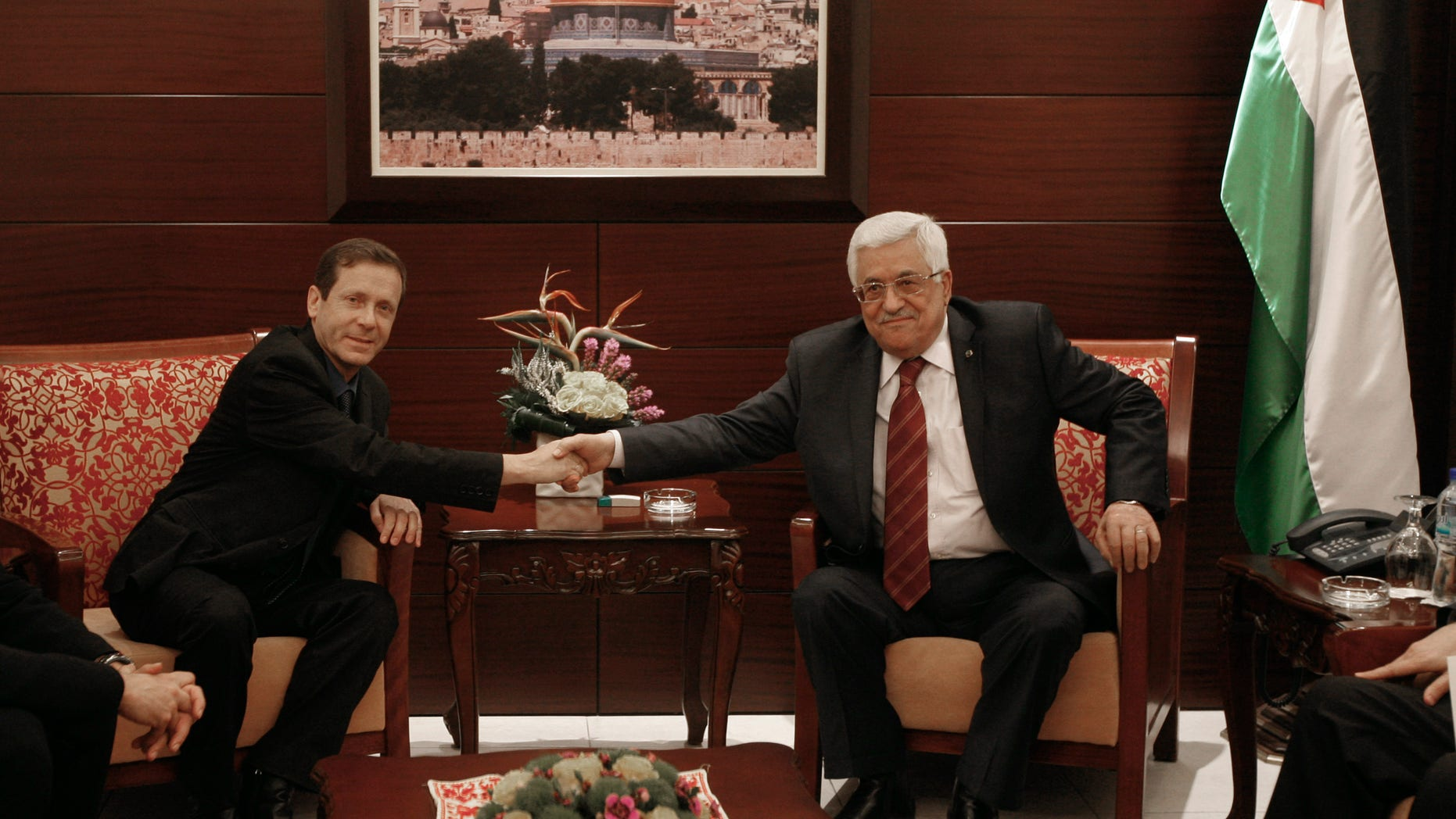 Israeli new Labor Party leader Isaac Herzog, left, shakes hands with the Palestinian President Mahmoud Abbas during their meeting in the West Bank city of Ramallah, Sunday, Dec. 1, 2013. (AP Photo/Majdi Mohammed)