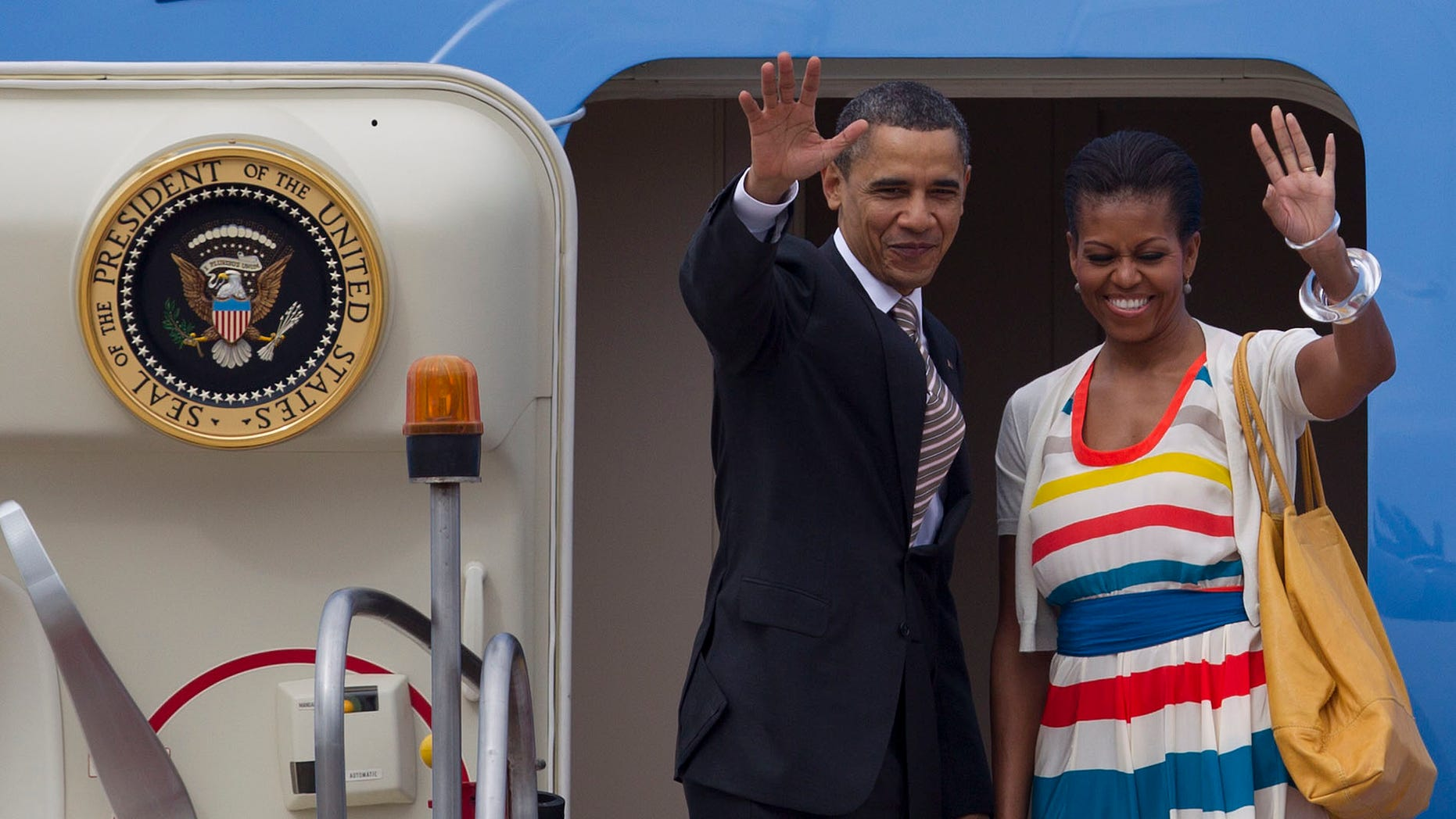 President Barack Obama, left, and his wife first lady Michelle Obama wave as they leave Rio de Janeiro, Brazil, Monday, March 21, 2011. Obama and his family flew to Santiago, Chile, on Monday morning. (AP Photo/Felipe Dana)