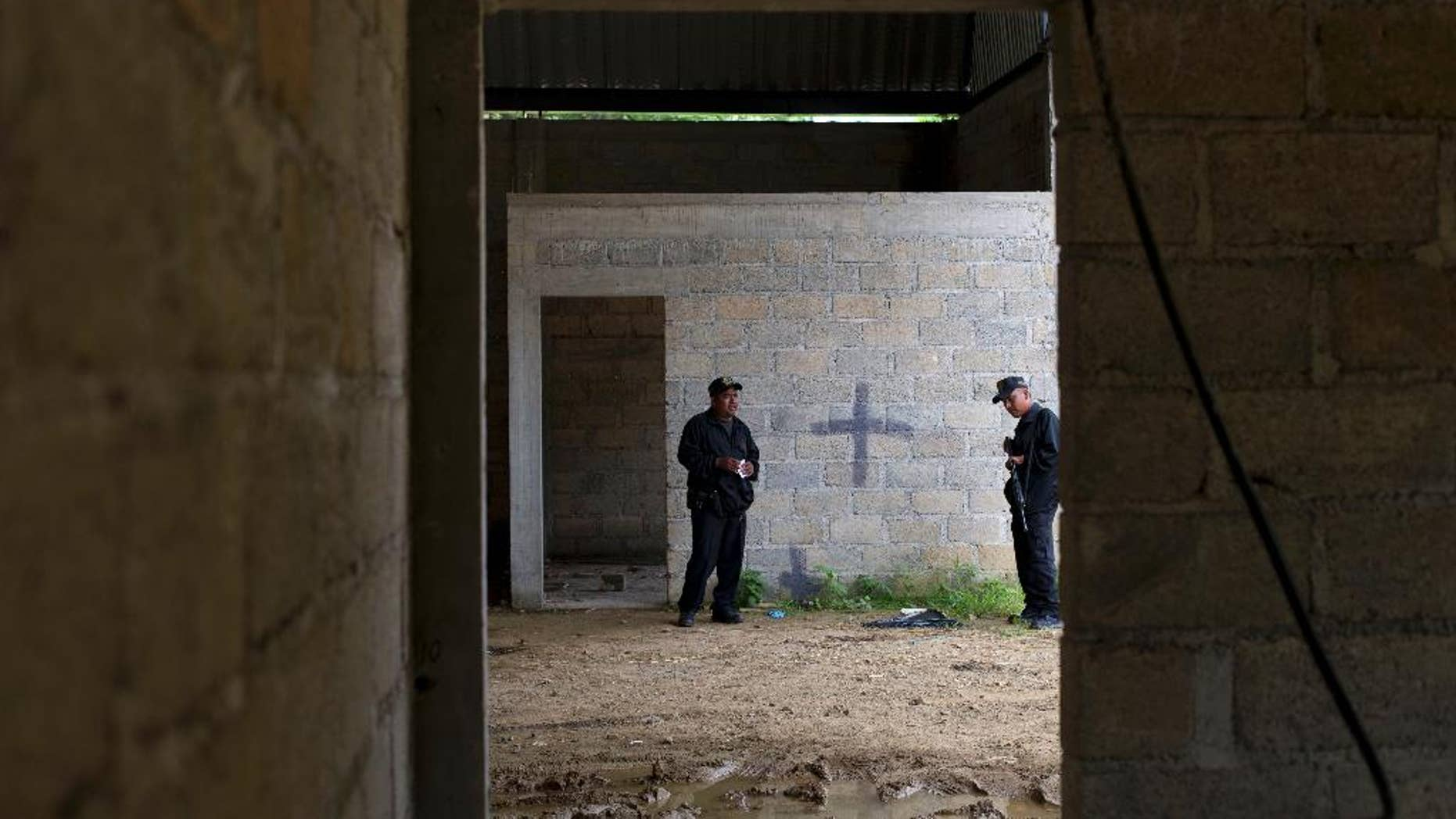 FILE - In this July 3, 2014, file photo, state police stand inside a warehouse where a black cross covers a wall near blood stains on the ground, after a shootout between Mexican soldiers and alleged criminals on the outskirts of the village of San Pedro Limon, in Mexico state, Mexico. Officials said Sunday Nov. 1, 2014, that seven Mexican soldiers have been charged with crimes ranging from homicide to improper conduct in connection with the shooting deaths of suspected gang members at a rural warehouse on June 30. (AP Photo/Rebecca Blackwell, File)