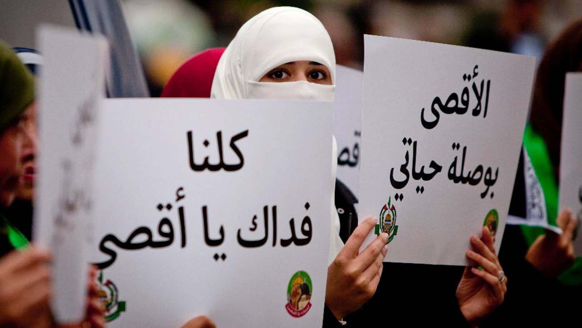 """Palestinian supporters of the Islamist movement Hamas, hold a placards with the slogan written in Arabic, """"we are all your defenders Al-Aqsa,"""", and """"Al-Aqsa is the compass for my life"""" during a protest against recent Israeli restrictions at the Al-Aqsa Mosque, in the West Bank City of Ramallah, Friday, Oct. 17, 2014. (AP Photo/Majdi Mohammed)"""