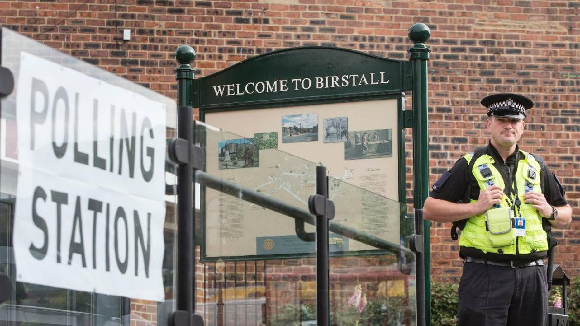 A police officer stands outside a polling station being used in the EU referendum at Birstall library, West Yorkshire, England Thursday June 23, 2016 near to where Labour MP Jo Cox was attacked and killed outside her constituency surgery. Voters in Britain are deciding Thursday whether the country should remain in the European Union. (Danny Lawson/PA via AP) UNITED KINGDOM OUT - NO SALES - NO ARCHIVE