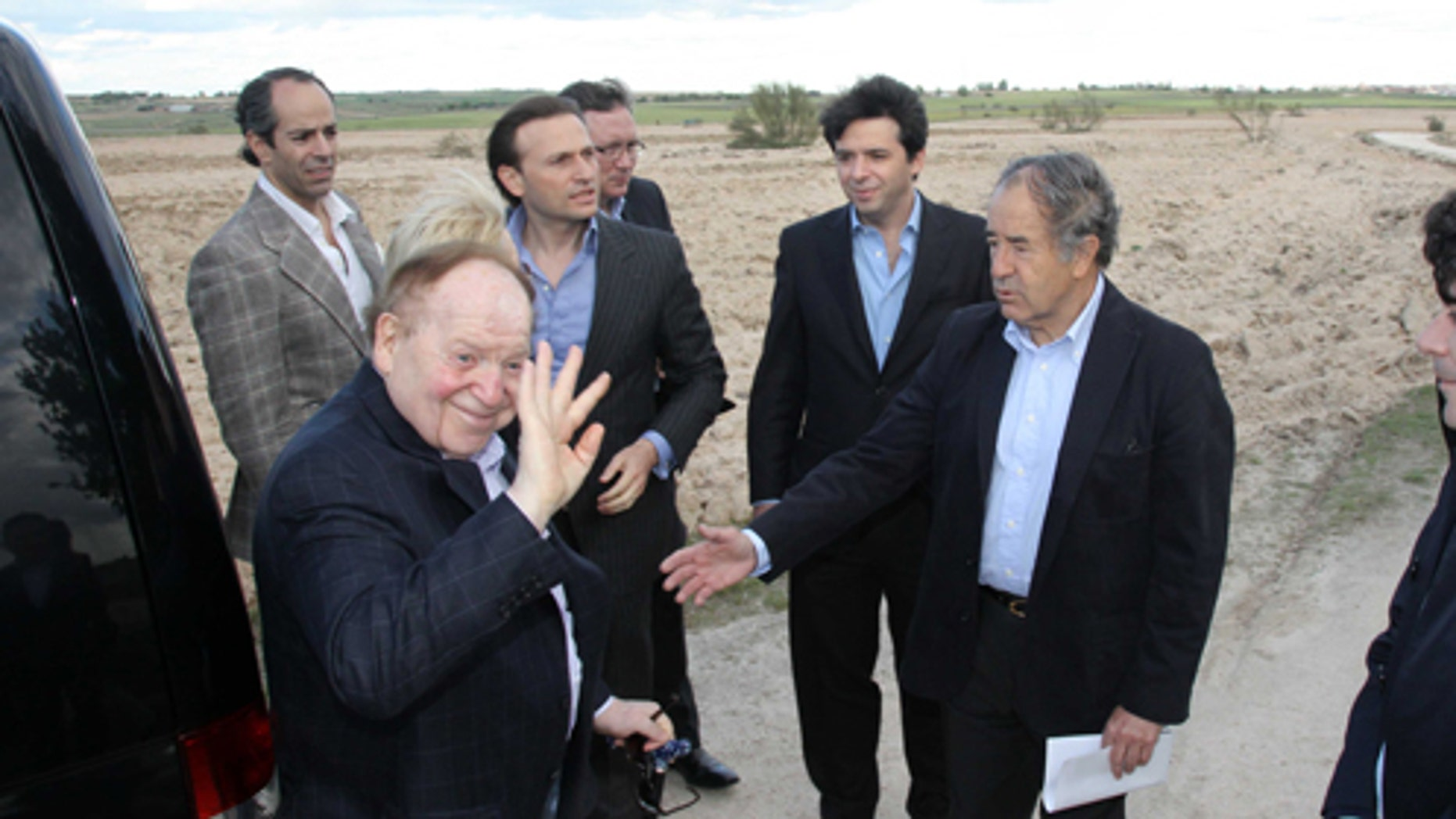 In this photo released by the Madrid Regional Government on May 6,  2012,  CEO of Las Vegas Sands Corp. Sheldon Adelson, left in foreground, waves while visiting Alcorcon, which was one of the possible sites for the EuroVegas project on the outskirts of Madrid, with others unidentified. (AP Photo/Comunidad de Madrid)