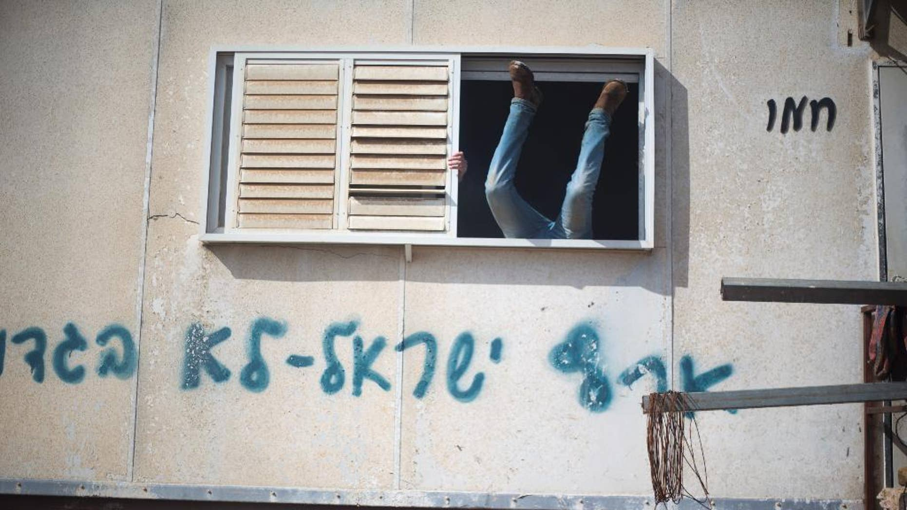 """A settler jumps into a trailer in Amona outpost in the West Bank, Wednesday, Feb. 1, 2017. Israeli forces have begun evacuating a controversial settlement  Amona, which is the largest of about 100 unauthorized outposts erected in the West Bank without permission but generally tolerated by the Israeli government. The writing reads: """"Eretz Israel we did not  betray """". (AP Photo/Ariel Schalit)"""