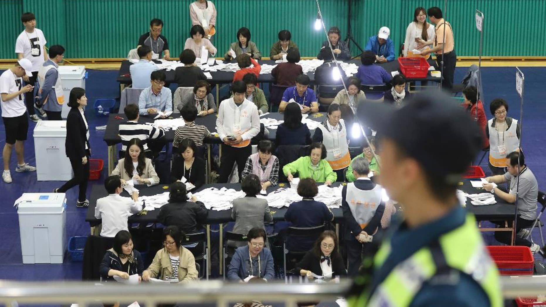 South Korean National Election Commission officials sort out ballots in the country's presidential election as a police officer stand guard in Seoul, South Korea, Tuesday, May 9, 2017. Two major challengers for South Korean president, a conservative and a centrist, conceded defeat Tuesday, paving the way for liberal Moon Jae-in to claim victory in an election that followed months of political turmoil caused by ousted President Park Geun-hye's corruption scandal. (AP Photo/Lee Jin-man)