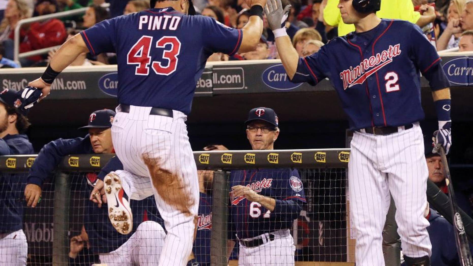 Minnesota Twins' Josmil Pinto, left, is congratulated by Brian Dozier after he scored on a single by Minnesota Twins' Eduardo Escobar off Arizona Diamondbacks pitcher Andrew Chafin in the second inning of a baseball game, Tuesday, Sept. 23, 2014, in Minneapolis. (AP Photo/Jim Mone)