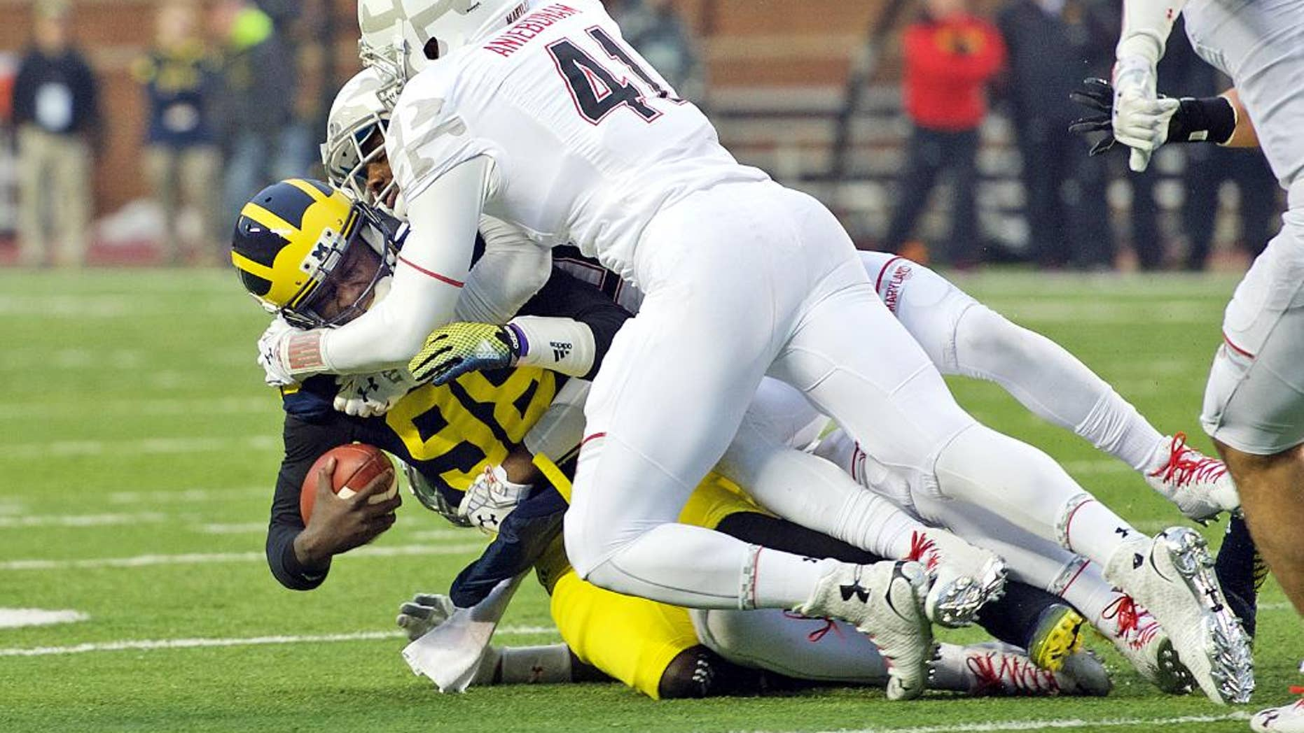 Michigan quarterback Devin Gardner, bottom left, gets sacked by Maryland linebackers Yannick Ngakoue, back, and Jesse Aniebonam (41), in the second quarter of an NCAA college football game in Ann Arbor, Mich., Saturday, Nov. 22, 2014. Maryland won 23-16. (AP Photo/Tony Ding)