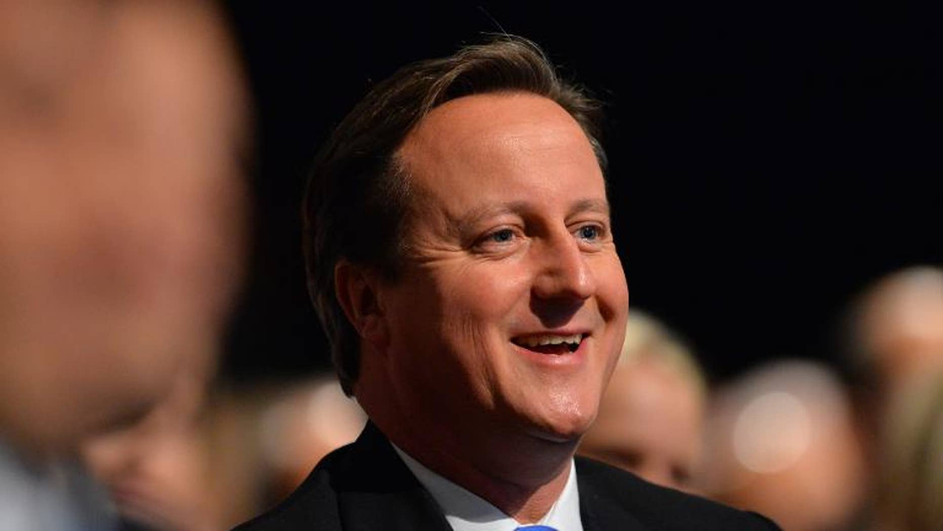 British Prime Minister David Cameron laughs as he listens to a speech by London Mayor Boris Johnson at the annual Conservative Party Conference in Manchester, on October 1, 2013
