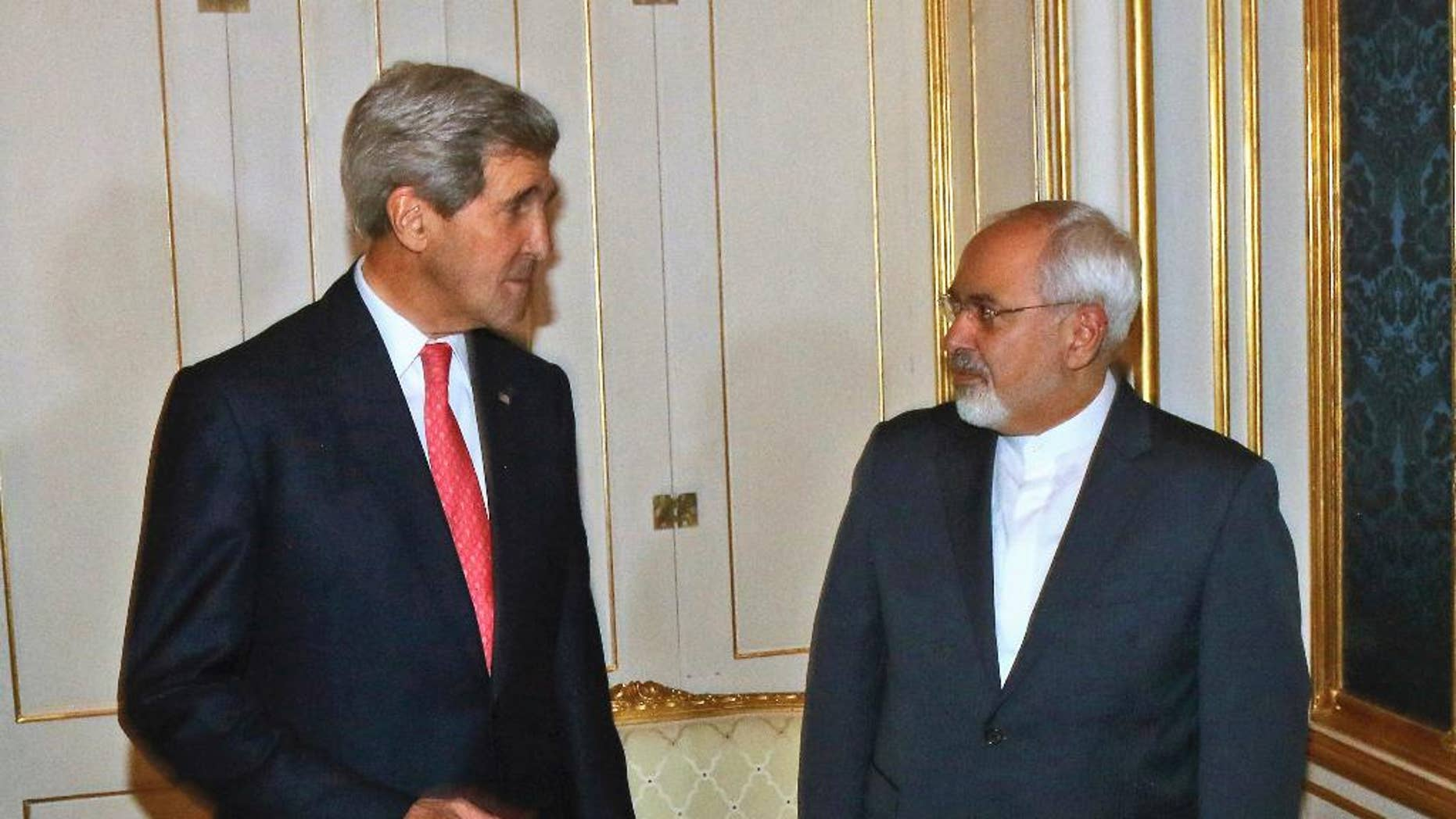 FILE - In this Nov. 23, 2014 file-pool photo, Secretary of State John Kerry talks with Iranian Foreign Minister Mohammad Javad Zarif in Vienna, Austria. Kerry plans to see Zarif this week amid Iranian complaints that it's not getting the sanctions relief it deserves under last year's landmark nuclear deal. (AP Photo/Ronald Zak, File-Pool)