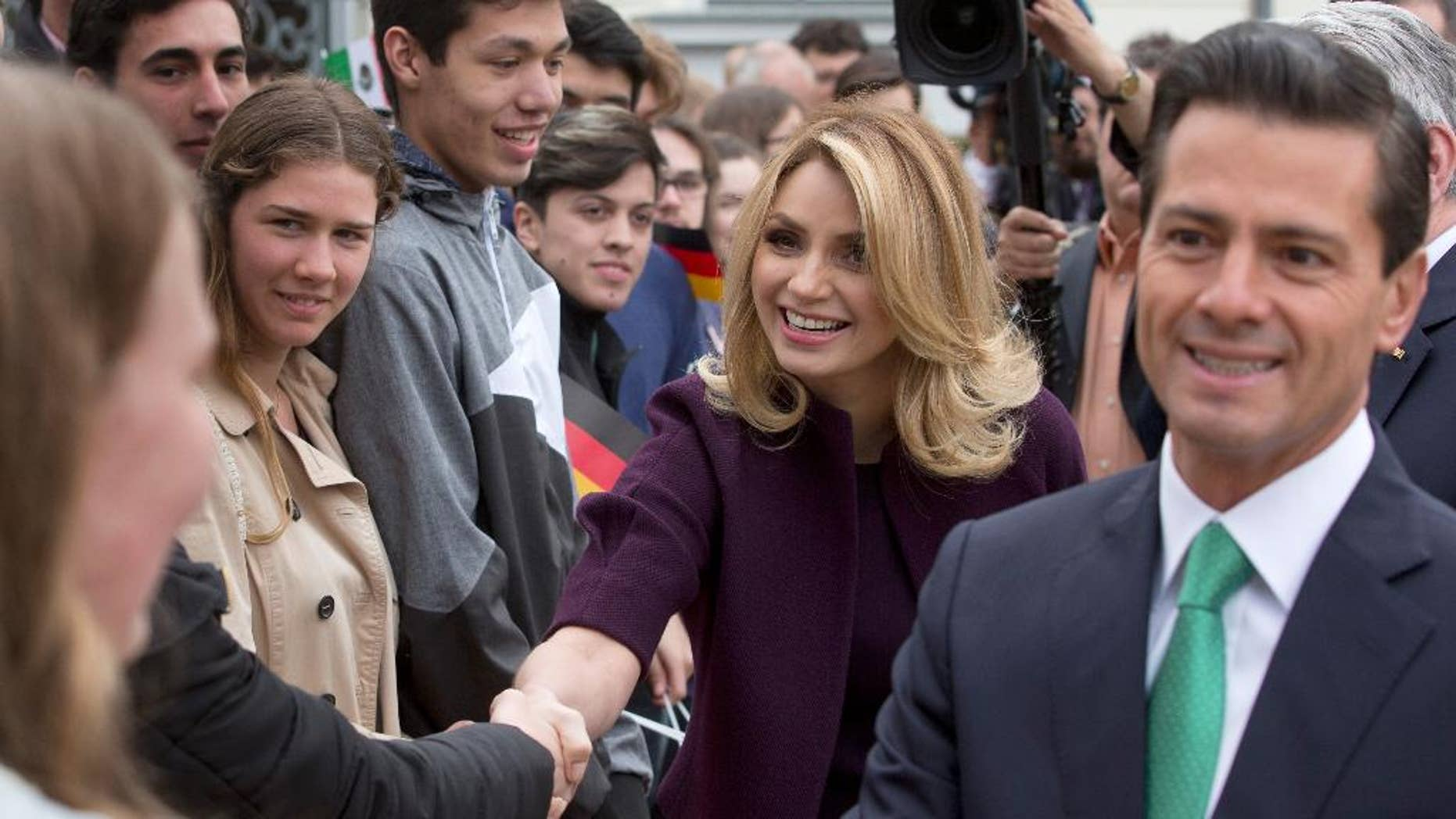FILE - In this April 11, 2016 file photo, Mexico's President Enrique Pena Nieto, right, and his wife Angelica Rivera de Pena greet students as they arrive to meet with Germany's President Joachim Gauck at Bellevue Palace in Berlin, Germany.  Pena Nieto apologized on Monday, July 18, 2016 for a 2014 scandal involving a mansion his wife bought from a firm that won lucrative contracts with his administration. (AP Photo/Michael Sohn, File)