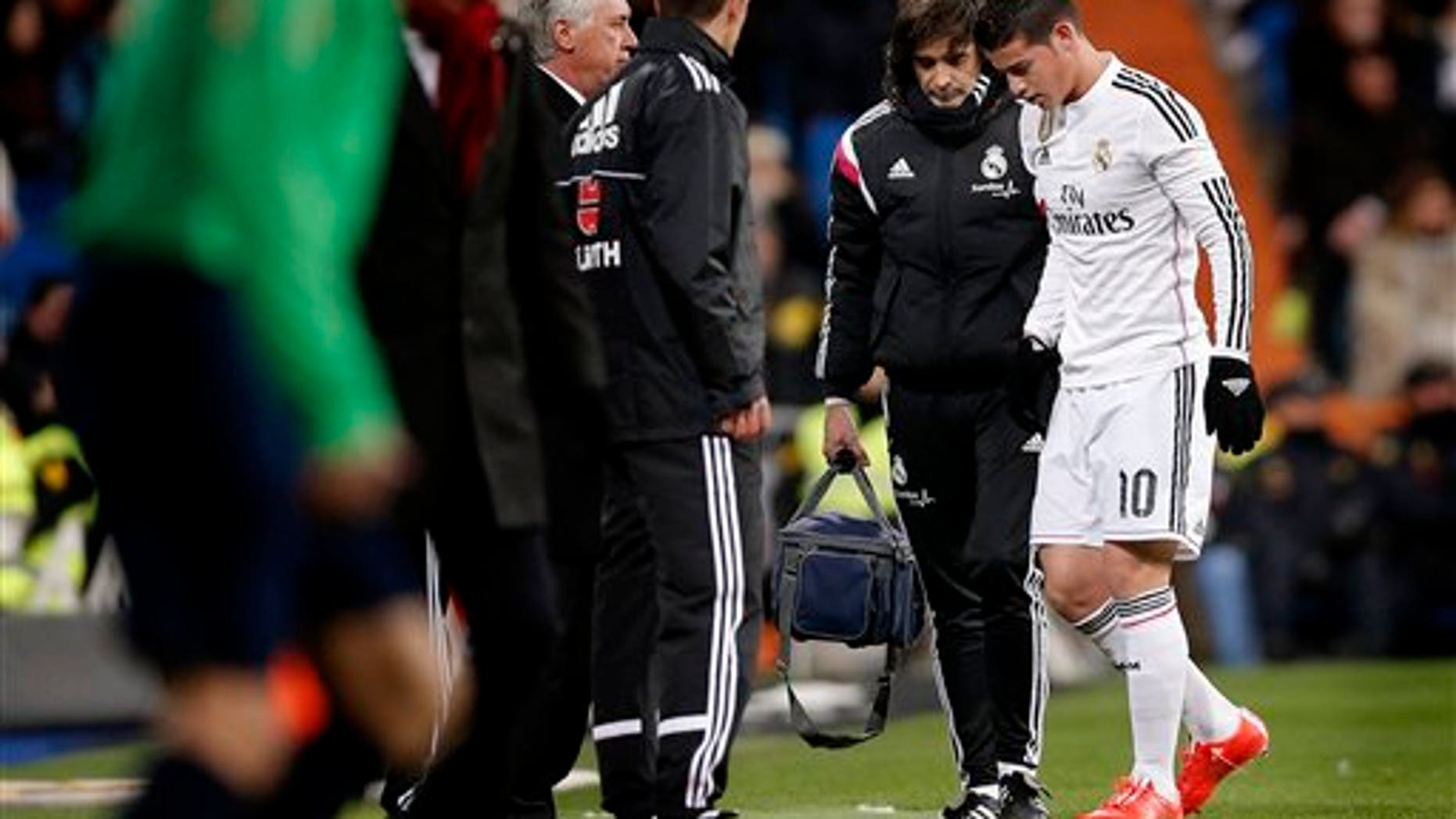 In this Feb. 4, 2015 picture James Rodriguez from Colombia, right, leaves the field injured during a La Liga soccer match between Real Madrid and Sevilla at the Santiago Bernabeu stadium in Madrid, Spain. James Rodriguez will get surgery on his right foot after Real Madrid confirmed a broken a metatarsal bone, who could be out for two or three months. (AP Photo/Daniel Ochoa de Olza)
