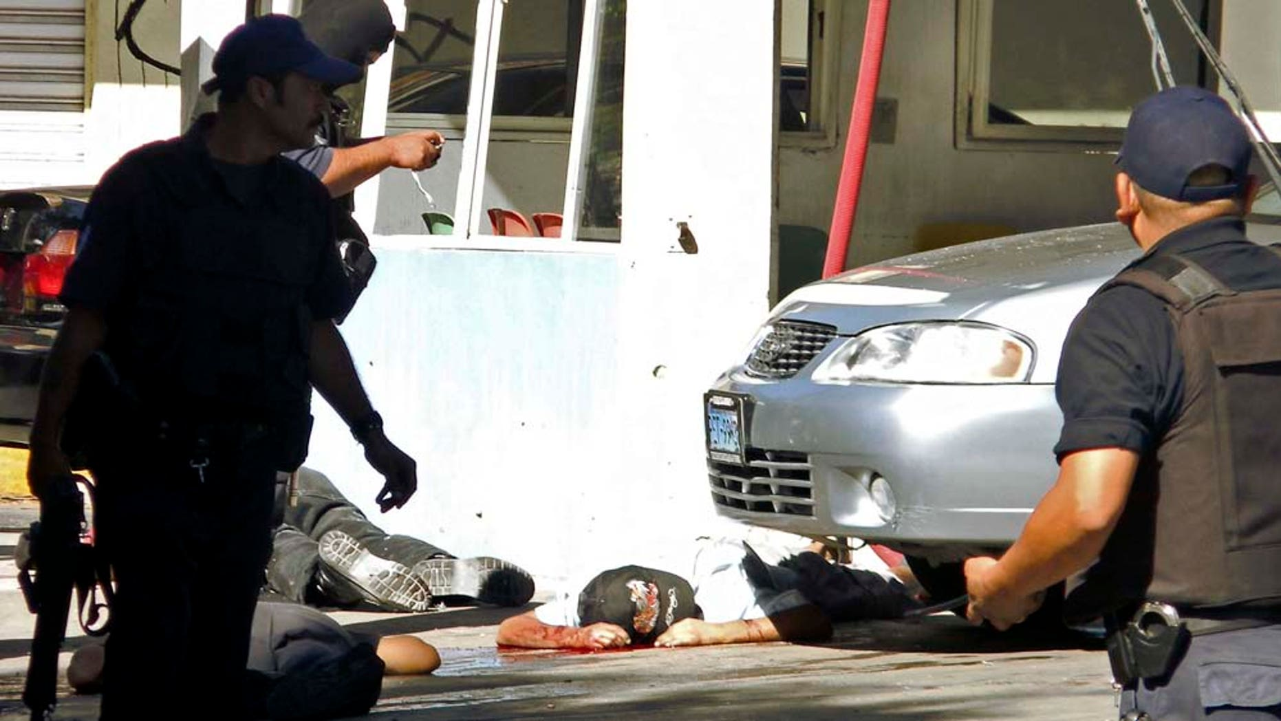 **  EDS NOTE GRAPHIC CONTENT  **  Police officers secure the area where 15 men were shot to death by unknown gunmen at a car wash in Tepic, Mexico, Wednesday, Oct. 27, 2010. This  was the third massacre in Mexico in less than a week. (AP Photo/Nayarit en Linea)