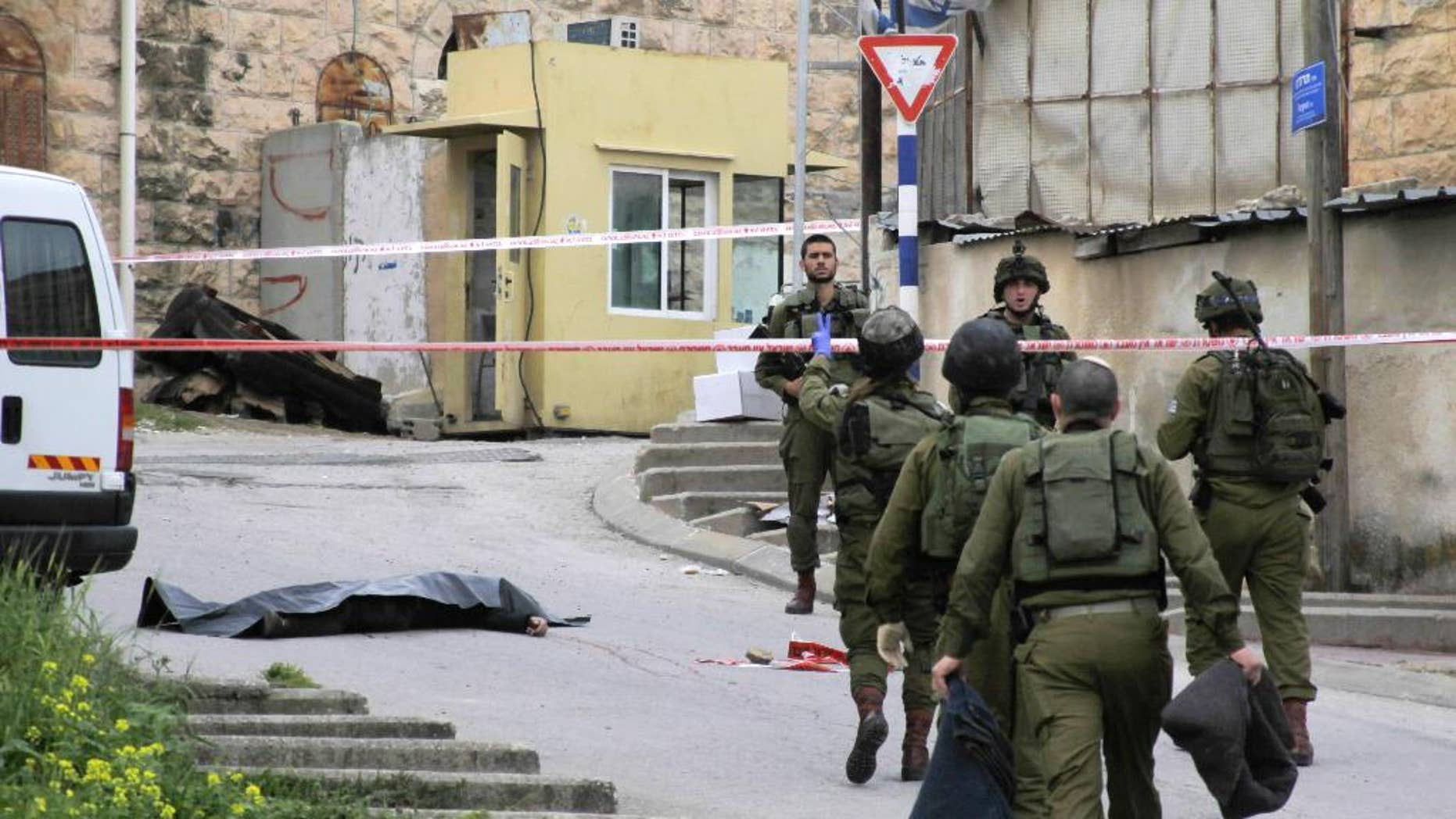 FILE - In this Thursday, March 24, 2016 file photo, Israeli soldiers stand near the body of a Palestinian who was shot and killed by a soldier while laying wounded on the ground after a stabbing attack in Hebron, West Bank.  Israeli Prime Minister Benjamin Netanyahu defended the military Sunday, March 27, 2016 following uproar over footage of a soldier lethally shooting a Palestinian attacker who had already been shot and subdued. (AP Photo, File)