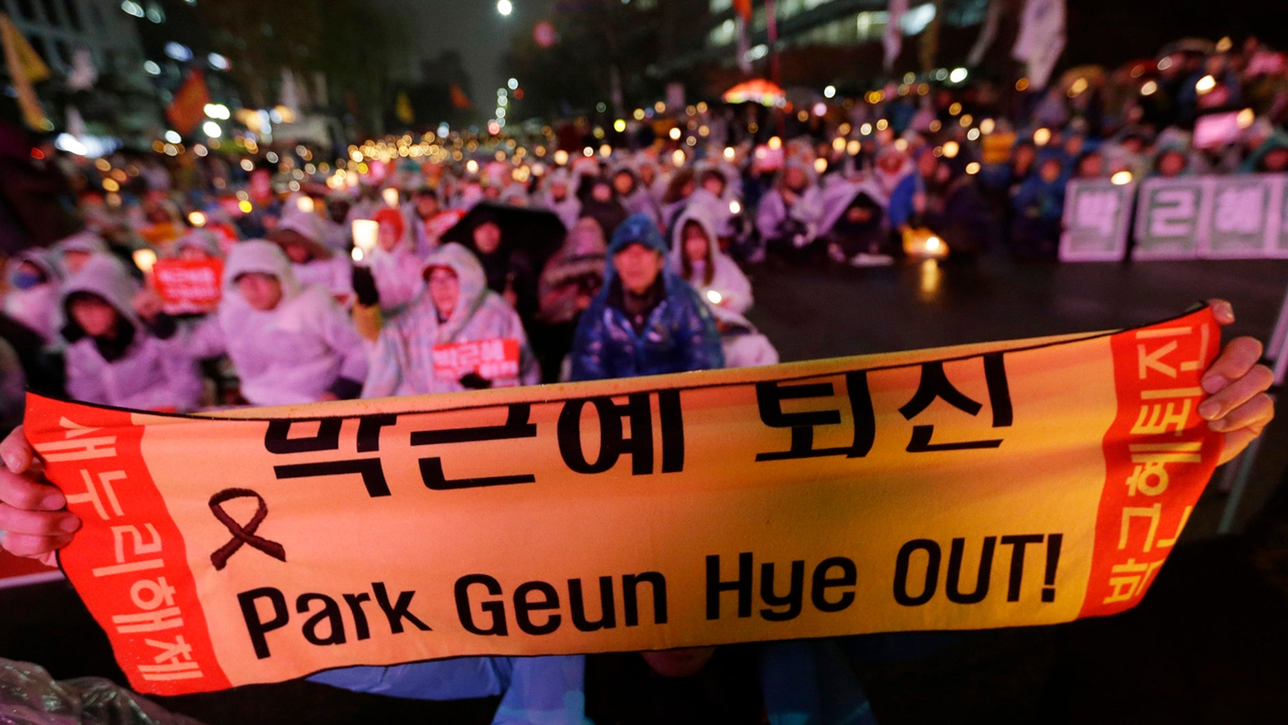 A protester holds up a banner during a rally demanding the impeachment of South Korean President Park Geun-hye near the National Assembly in Seoul, South Korea, Thursday, Dec. 8, 2016.