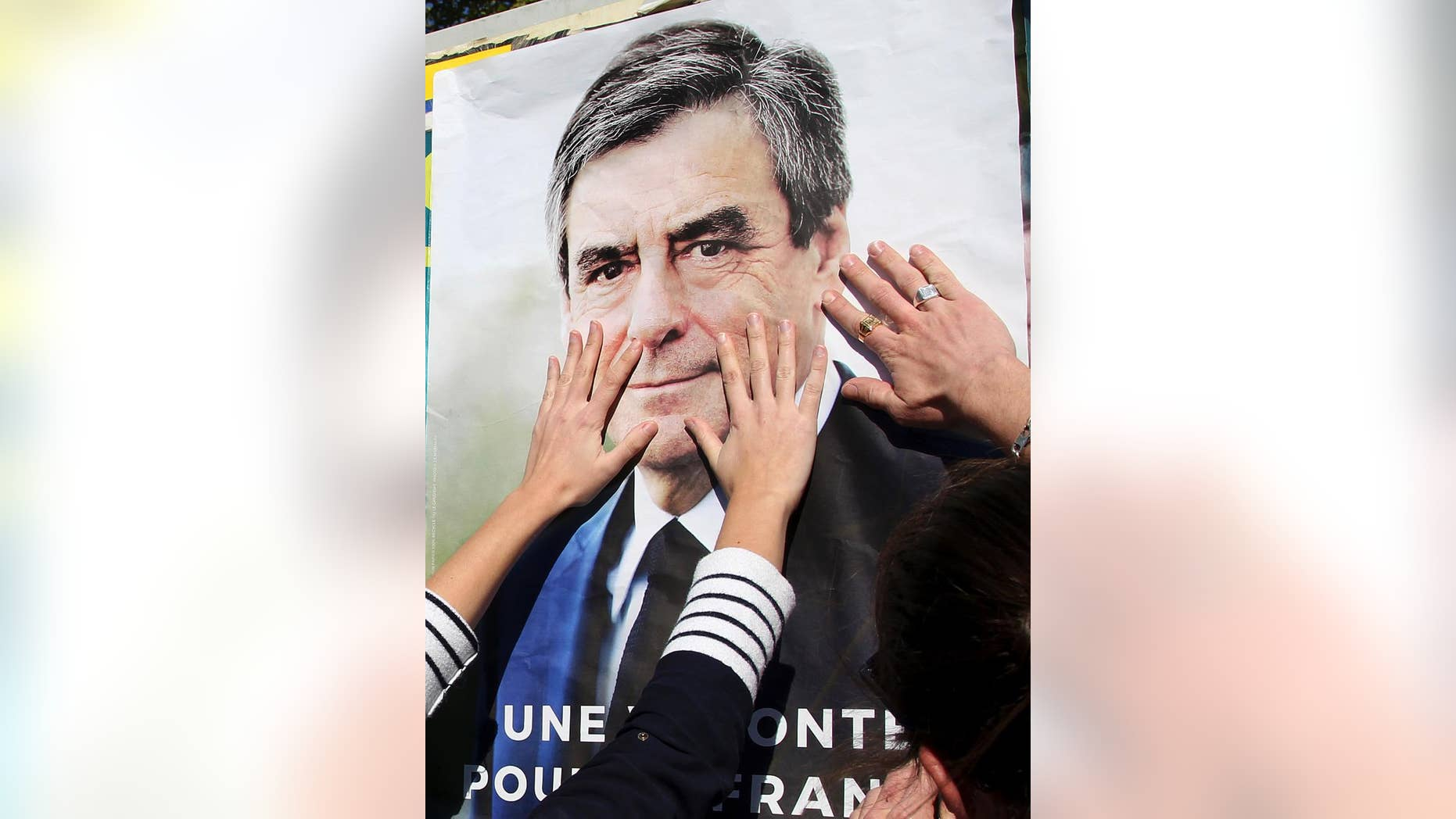 Supporters of conservative presidential candidate Francois Fillon glue a campaign poster in Bayonne, southwestern France, Wednesday, April 19, 2017. The two-round presidential election is set for April 23 and May 7. (AP Photo/Bob Edme)