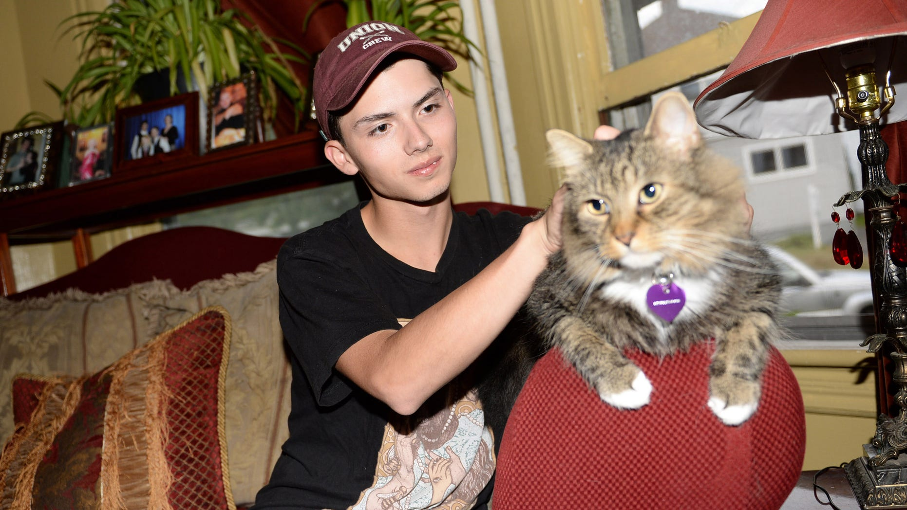 FILE - In a Wednesday, Sept. 10, 2014 file photo, Draven Rodriguez and his cat Mr. Bigglesworth at their home in Schenectady, N.Y. Rodriguezâs parents tell the Times-Union of Albany their son committed suicide Thursday, Feb. 19, 2015 at their Schenectady home. He was 17. Rodriguez had wanted his senior yearbook portrait to show him holding his cat Mr. Bigglesworth, with lasers in the background.  The school denied his request but said the photo could appear somewhere in the Schenectady High School yearbook.(AP Photo/The Daily Gazette, Patrick Dodson)