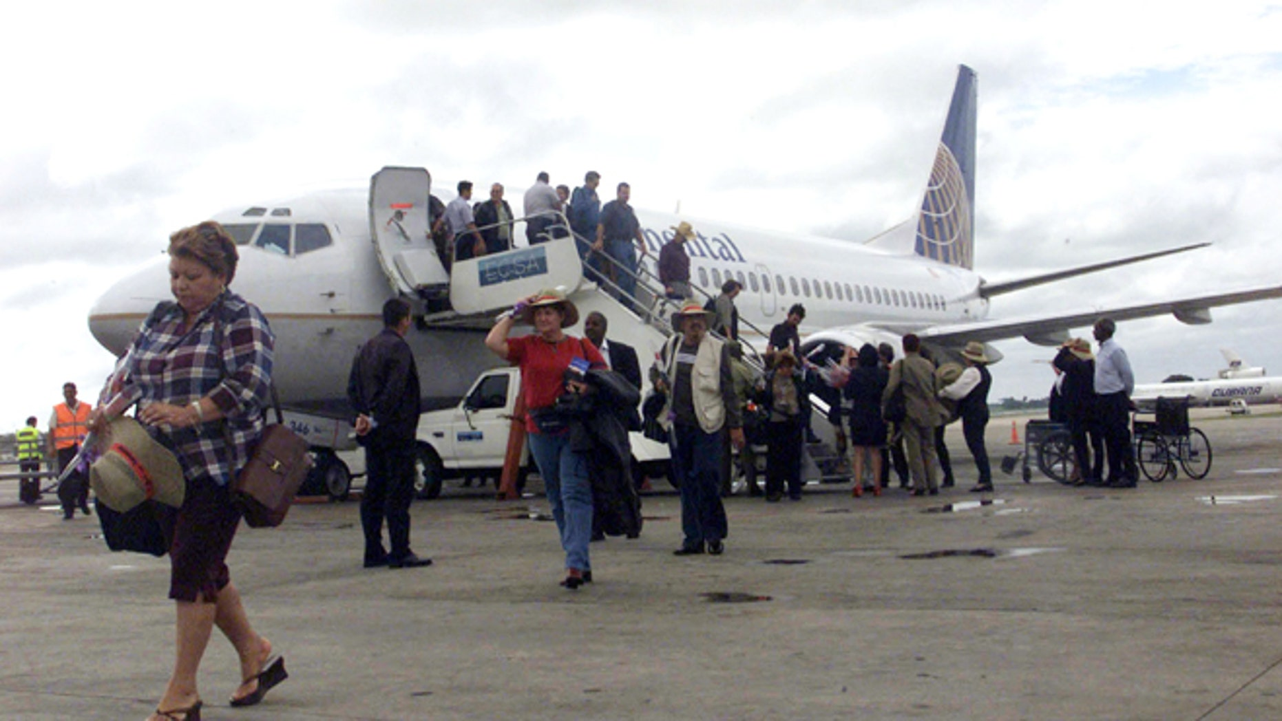 Passengers walk away from a Continental Airlines Boeing-737 at Havana's Jose Marti International Airport. (Photo by Jorge Rey/Getty Images)