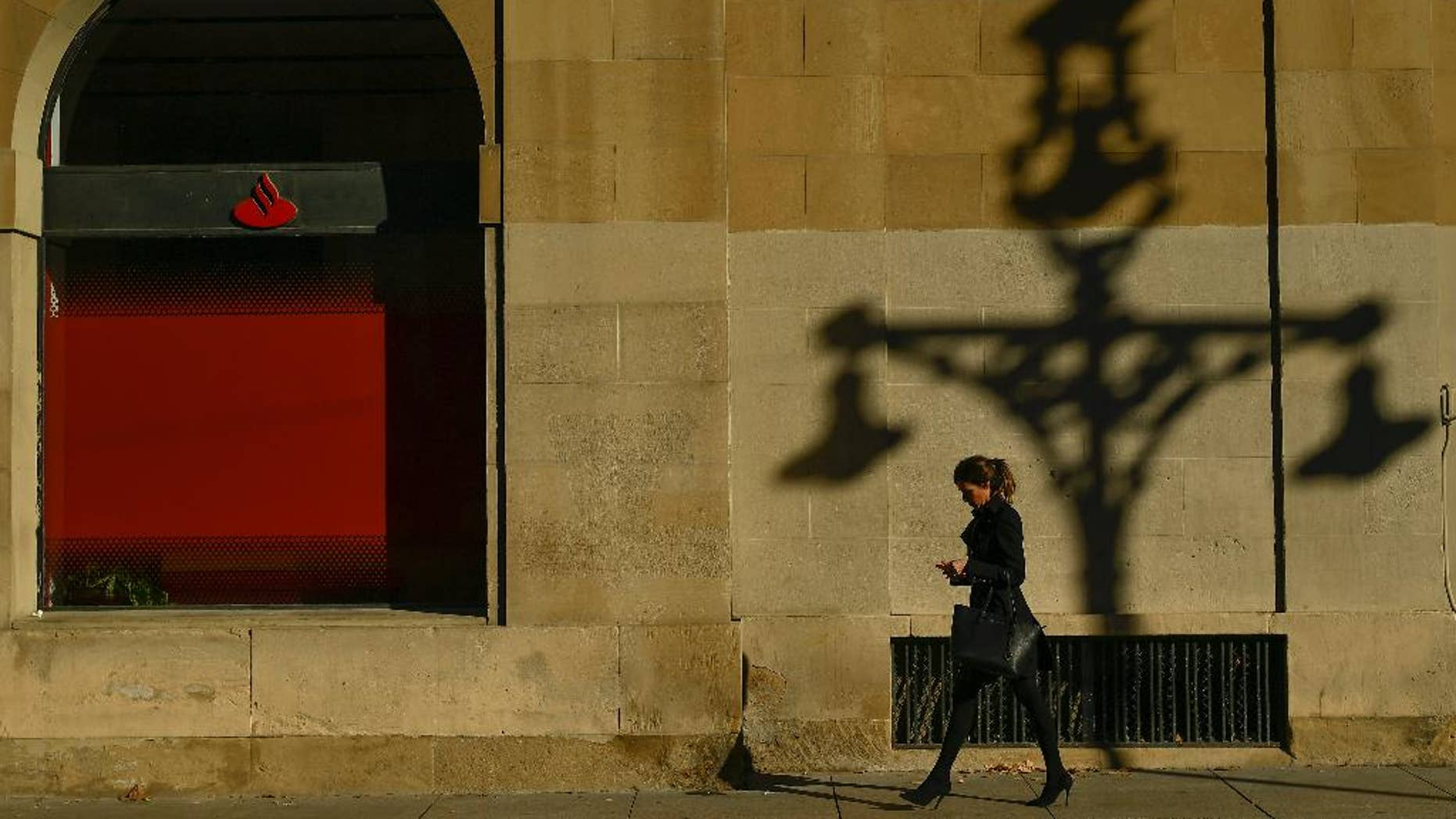 A woman walks past checking her personal phone beside a wall with the shadow of a street light,  during an autumn day, in Pamplona northern Spain, Thursday, Dec. 1, 2016. (AP Photo/Alvaro Barrientos)