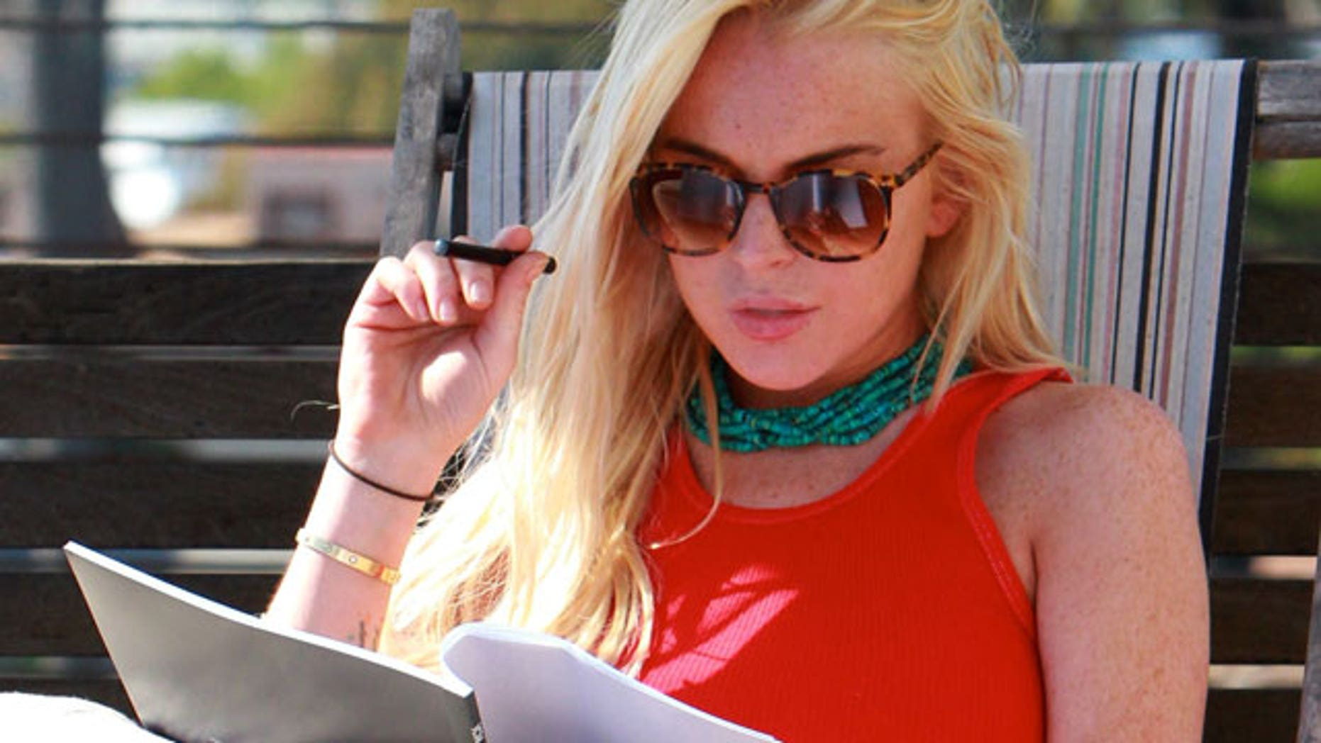 Lindsay Lohan reads scripts while serving out her house arrest sentencing. (X17 Online)