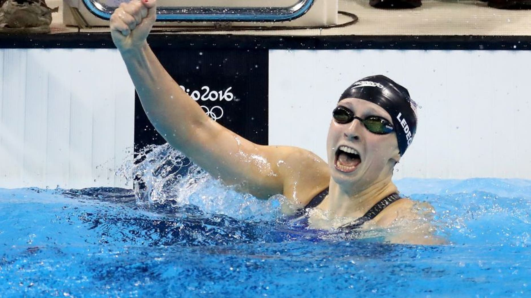 RIO DE JANEIRO, BRAZIL - AUGUST 07: Katie Ledecky of the United States celebrates winning gold and setting a new world record in the Women's 400m Freestyle Final on Day 2 of the Rio 2016 Olympic Games at the Olympic Aquatics Stadium on August 7, 2016 in Rio de Janeiro, Brazil. (Photo by Ryan Pierse/Getty Images)