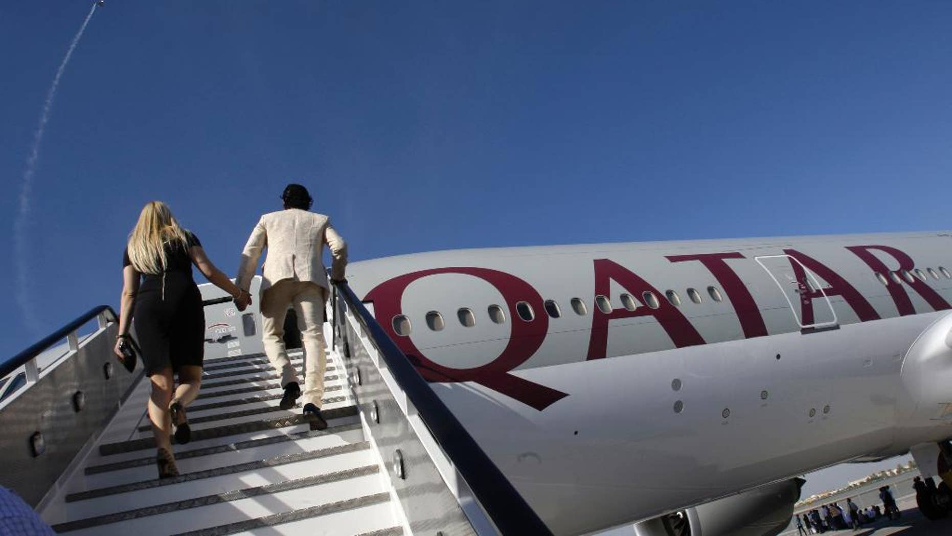 FILE - In this Nov. 14, 2011 file photo, visitors walk up stairs to inspect a Boeing 777-200LR aircraft in Qatar Airways livery at the Dubai Airshow in Dubai, United Arab Emirates. Qatar Airways has launched the world's longest scheduled commercial airline route with the arrival of its flight from Doha to Aukland, New Zealand. The Gulf carrier said flight QR920 touched down in Aukland early on Monday, Feb. 6, 2017, after covering a distance of 14,535 kilometers (9,032 miles). (AP Photo/Kamran Jebreili, File)