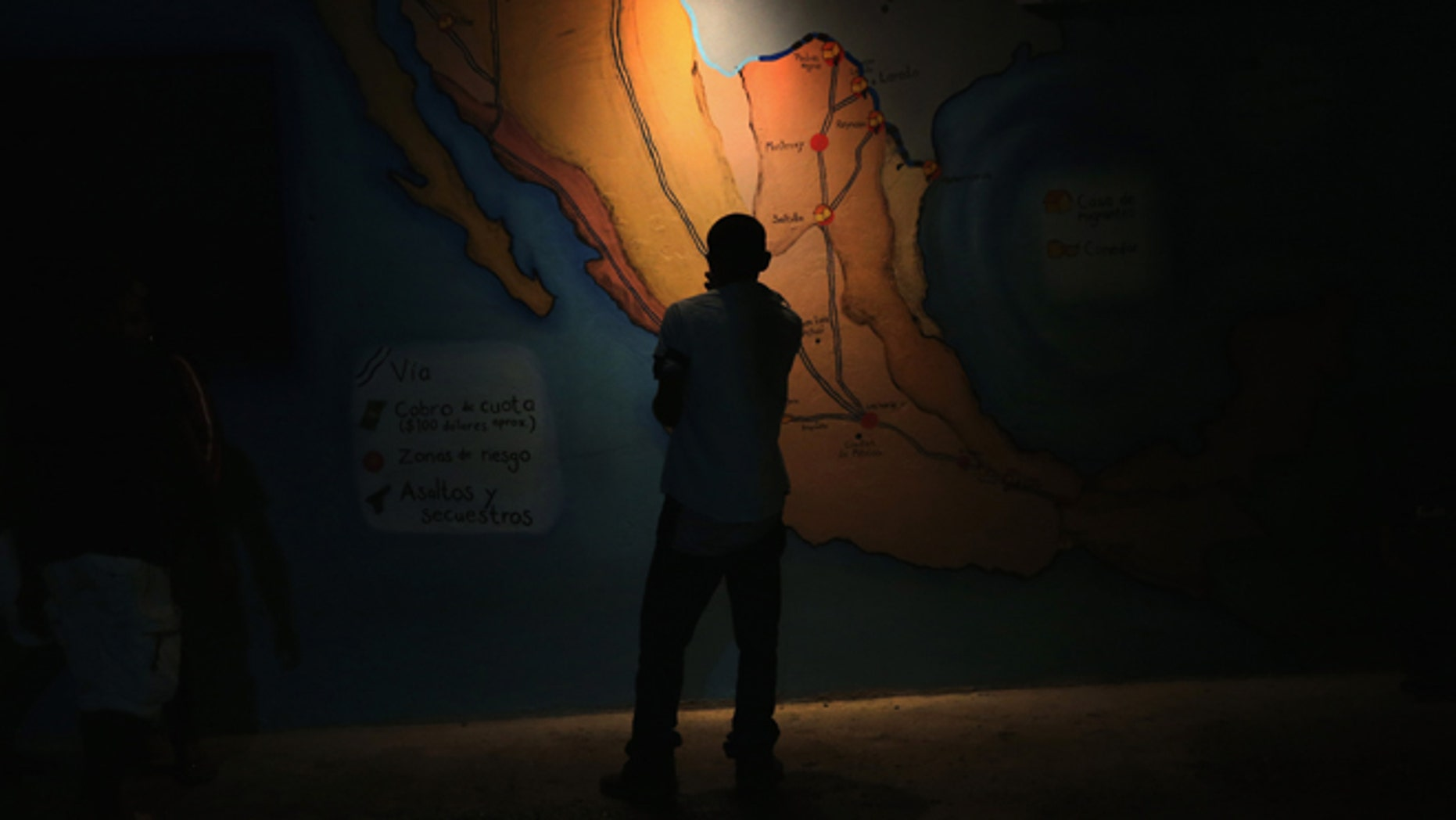 A Honduran immigrant inspects map of Mexico showing train routes leading north at a shelter for undocumented immigrants on September 14, 2014 in Tenosique, Mexico.(Photo by John Moore/Getty Images)