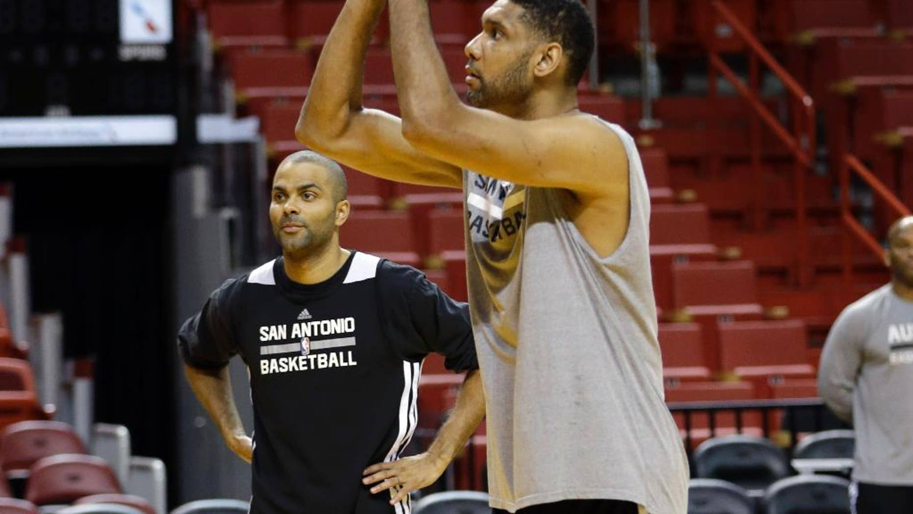 San Antonio Spurs' Tim Duncan, right, shoots as Tony Parker, left, looks on  during basketball practice at the NBA Finals, Wednesday, June 11, 2014, in Miami. The Spurs lead the Miami Heat 2-1 in the best-of-seven games series. (AP Photo/Lynne Sladky)