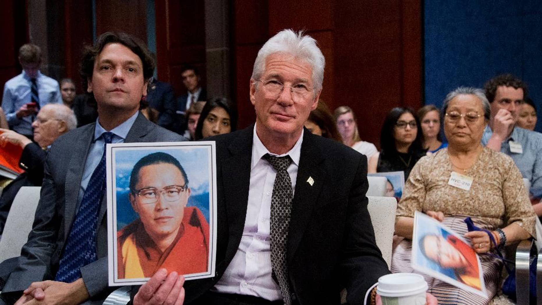 American actor and activist Richard Gere, with Matteo Mecacci, president of International Campaign for Tibet, left, holds a photo of Tulku Tenzin Delek Rinpoche, one of the most respected and revered Tibetan lamas, who passed away in custody in a Chinese prison on July 12, during a hearing on Tibet with the Tom Lantos Human Rights Commission, Tuesday, July 14, 2015, on Capitol Hill in Washington.   (AP Photo/Manuel Balce Ceneta)