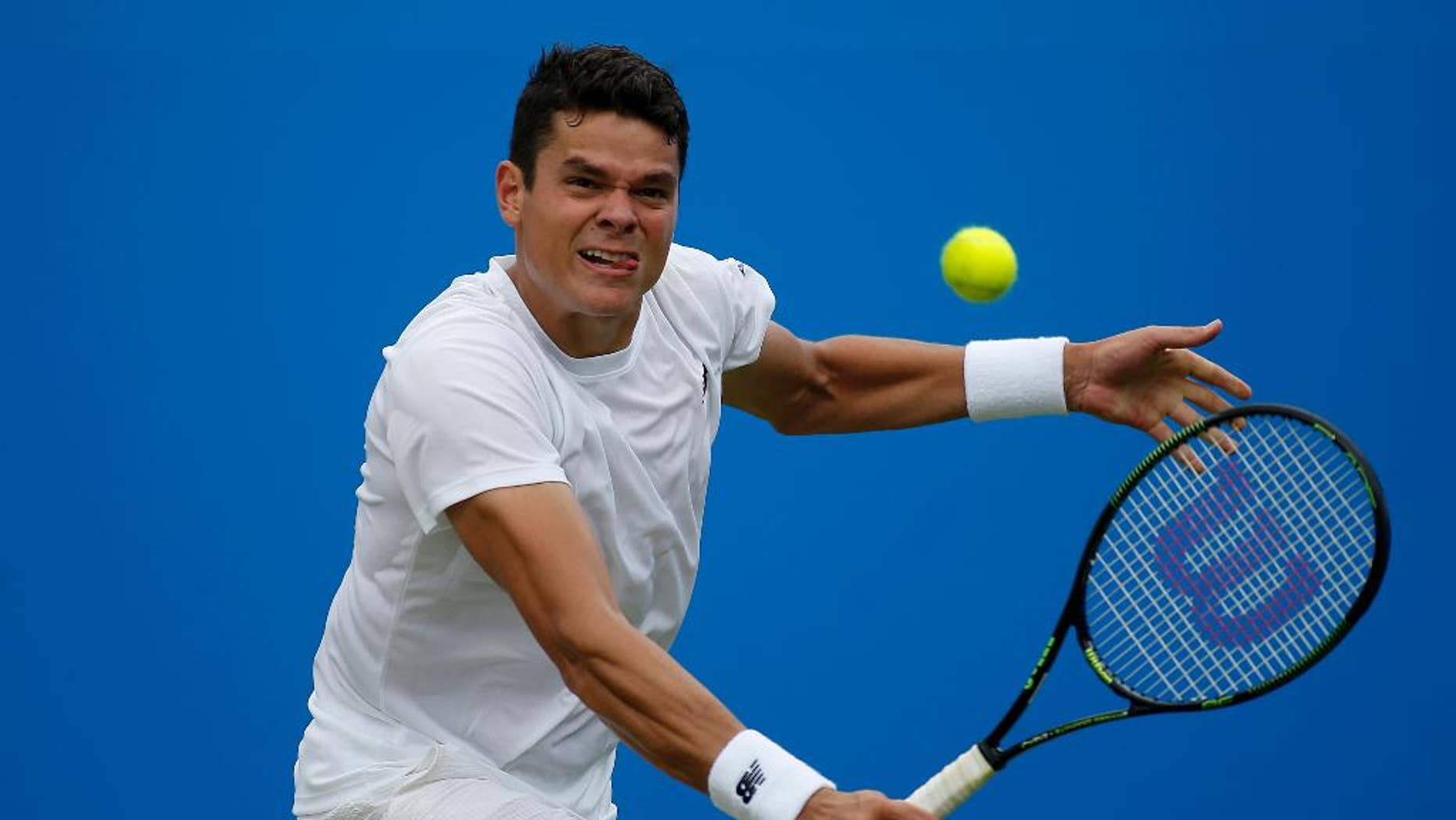 Canada's Milos Raonic makes a return to the Czech Republic's Jiri Vesely, during day four of the 2016 tennis Championships at The Queen's Club, London, Thursday June 16, 2016. (Steve Paston/PA via AP)  UNITED KINGDOM OUT