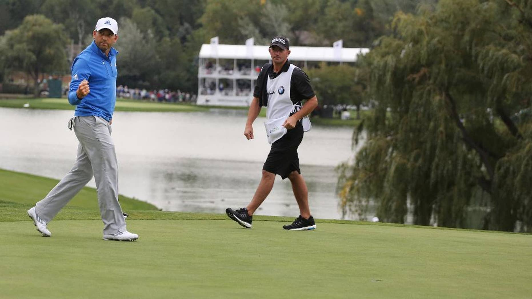 Sergio Garcia, left, of Spain, reacts after sinking his putt on the 18th hole for a birdie during the second round of the BMW Championship golf tournament at Cherry Hills Country Club in Cherry Hills Village, Colo., Friday, Sept. 5, 2014. (AP Photo/Brennan Linsley)