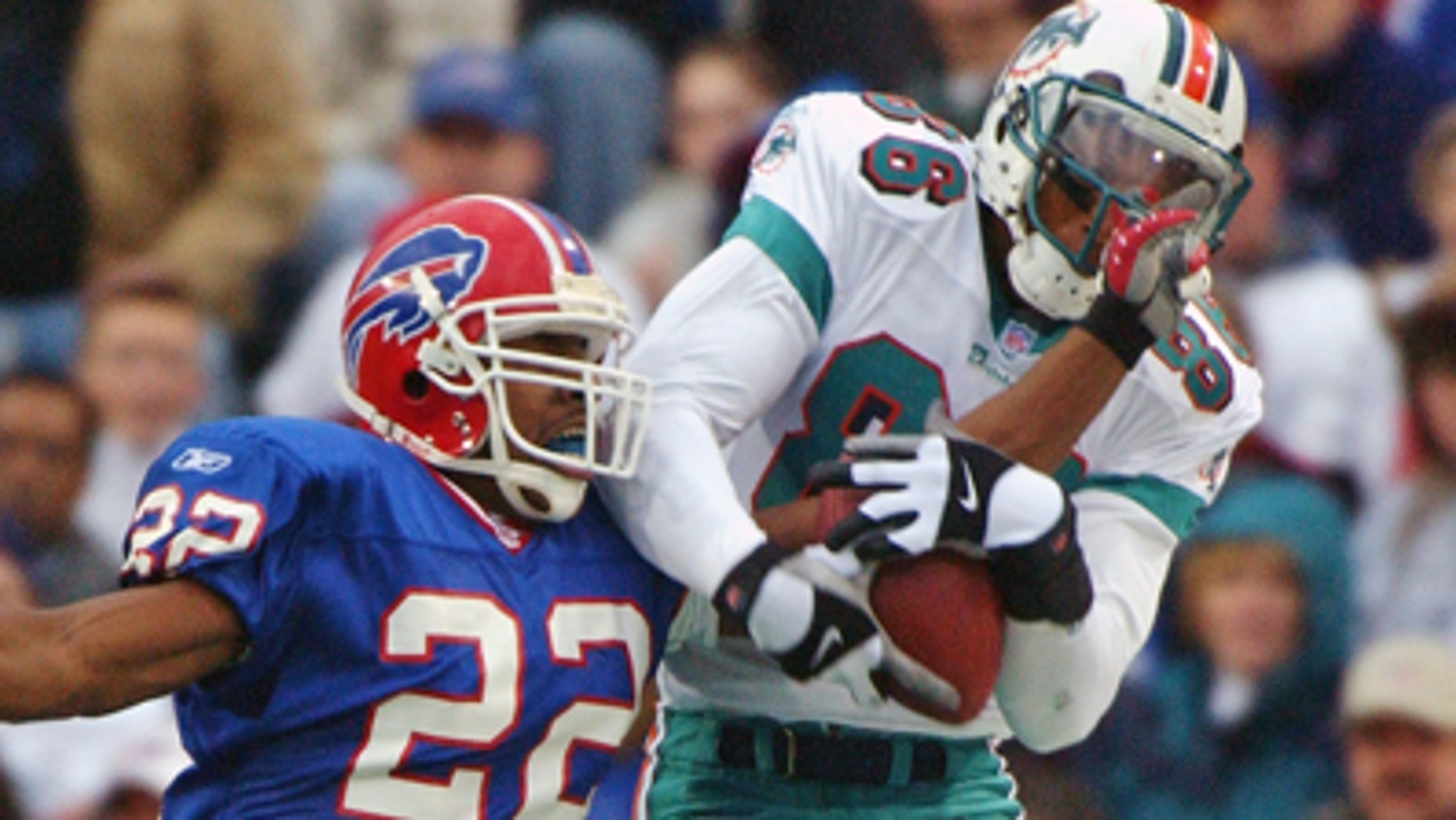 Nov. 25, 2001: Miami Dolphins' Oronde Gadsden, right, hauls in a pass under pressure from Buffalo Bills' Nate Clements during the second half of an NFL football game in Orchard Park, N.Y. Gadsden is one of nearly two dozen former NFL players that are suing the league over severe and permanent brain damage they say is linked to concussions suffered on the job. (AP)