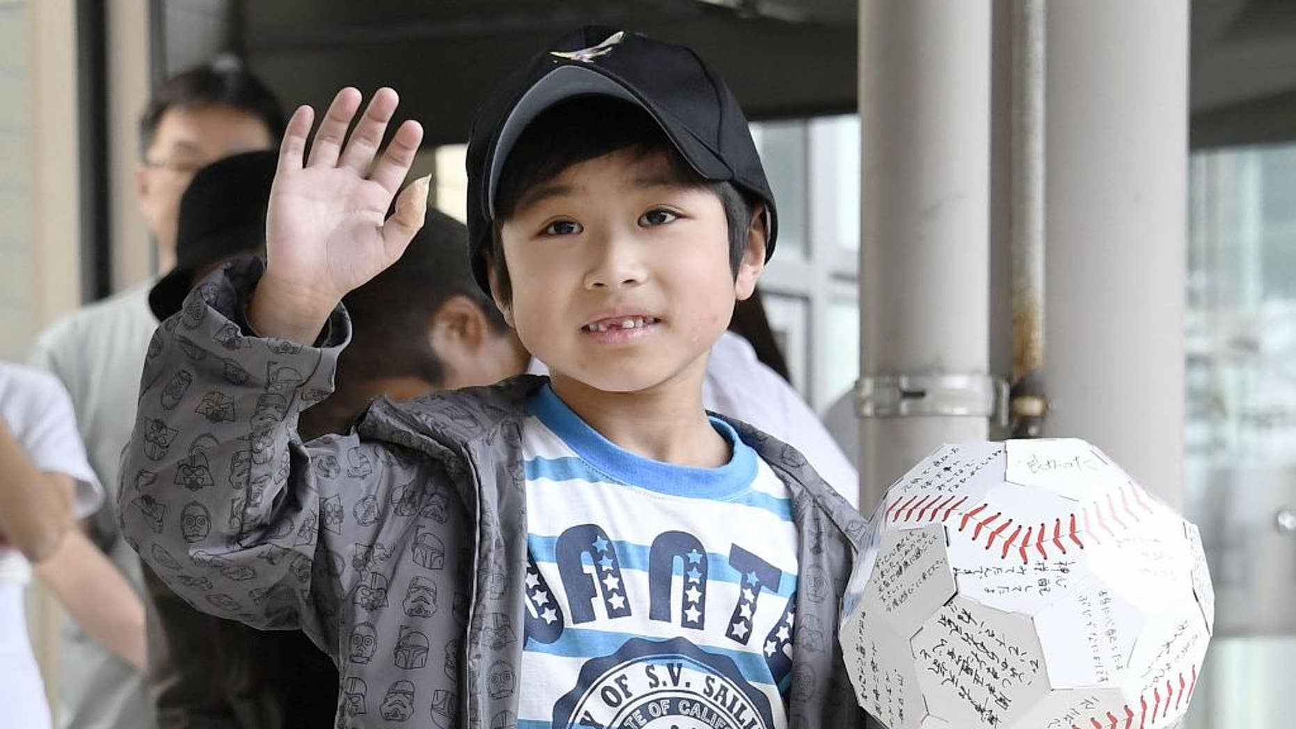 FILE - In this June 7, 2016 file photo, Yamato Tanooka, who survived almost a week in a forest after his parents left him at the side of a road,  waves as he leaves a hospital in Hakodate on the northern island of Hokkaido. The Japanese boy was released from a hospital this week, smiling and waving at a crowd cheering the happy ending. Public criticism of the father, who made 7-year-old Tanooka get out of the car to punish him for misbehavior, has faded, and police reportedly won't pursue charges. (Daisuke Suzuki/Kyodo News via AP, File) JAPAN OUT, MANDATORY CREDIT