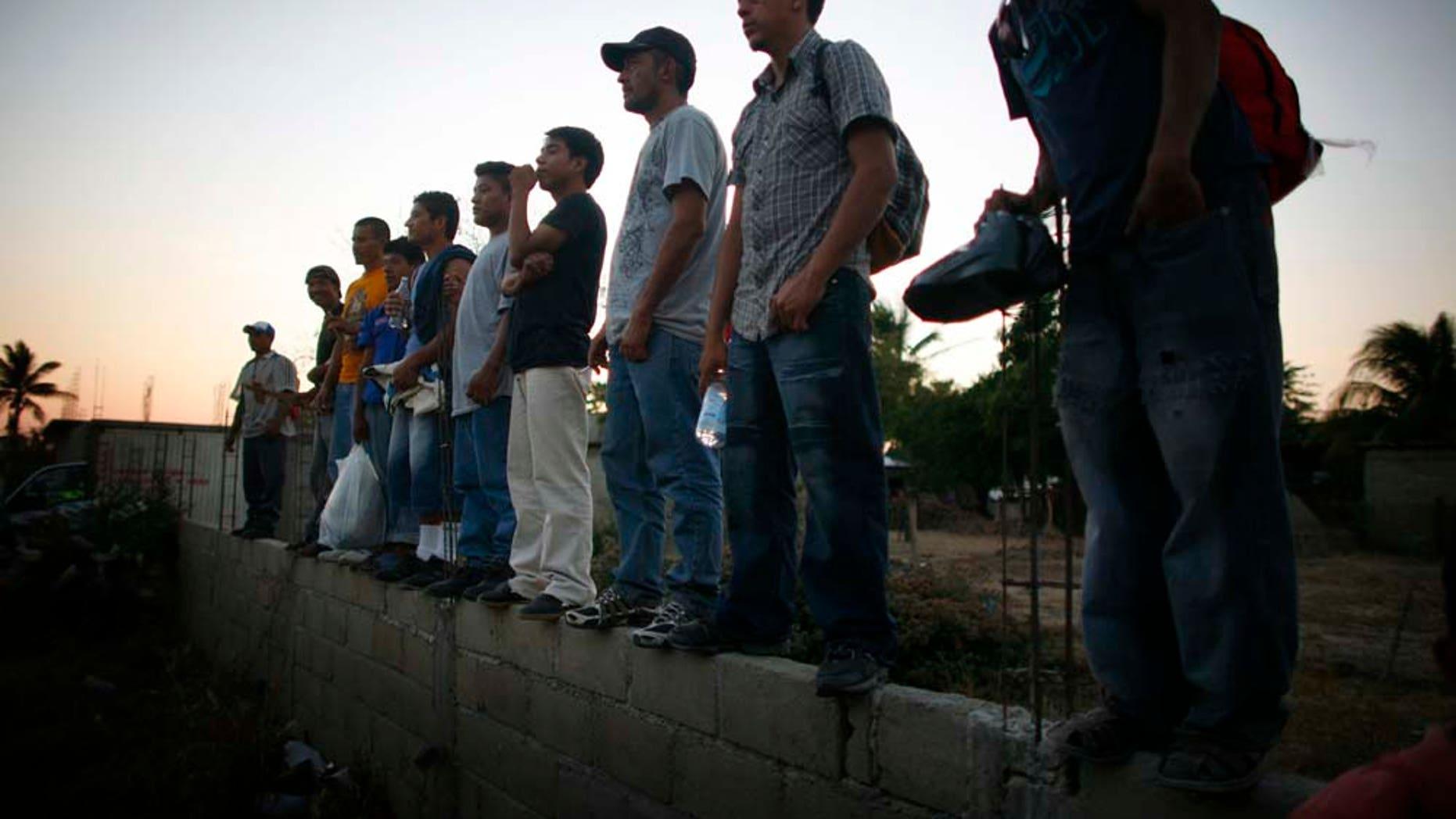 Migrantes centroamericanos esperan de pie afuera de la Casa del Migrante en Arriaga, Chiapas, el viernes 7 de enero del 2011. El tren más usado por los migrantes en su camino de este estado del sur de México hacia Estados Unidos no llegó el viernes a Arriaga y las autoridades locales hicieron un operativo sorpresa para escoltar a los migrantes a la frontera con el estado de Oaxaca. De acuerdo con varias organizaciones defensoras de los derechos de los migrantes, las autoridades detuvieron el tren en Oaxaca para sabotear una protesta programada para el viernes a bordo del tren. (Foto AP/Miguel Tovar)