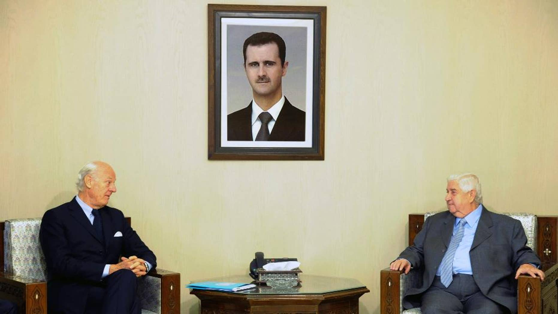 """In this photo released by the Syrian official news agency SANA, Syria's Foreign Minister Walid al-Moallem, right, meets with U.N. Special Envoy for Syria Staffan de Mistura in Damascus, Syria, Sunday, Nov. 1, 2015. Al-Moallem said """"important"""" points were made during international talks aimed at reviving the peace process but that negotiators failed to convince his government's foes to curb their support for """"terrorism."""" (SANA via AP)"""