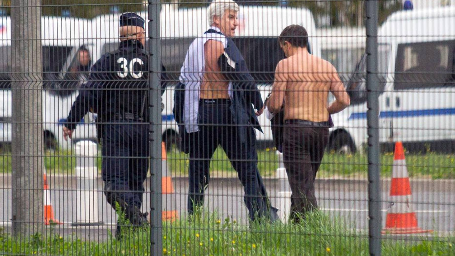FILE - In this Monday, Oct. 5, 2015 file photo, Air France director of Human Resources Xavier Broseta, right, and Air France assistant director of long-haul flights Pierre Plissonnier, center, are protected by a police officer as they flee Air France headquarters at Roissy Airport, north of Paris, France, after scuffles with union activists. A group of former Air France workers is going on trial for allegedly taking part in violence that erupted during a union protest last year at the airline's headquarters and left two executives fleeing over a fence with their shirts ripped off. (AP Photo/Jacques Brinon, File)