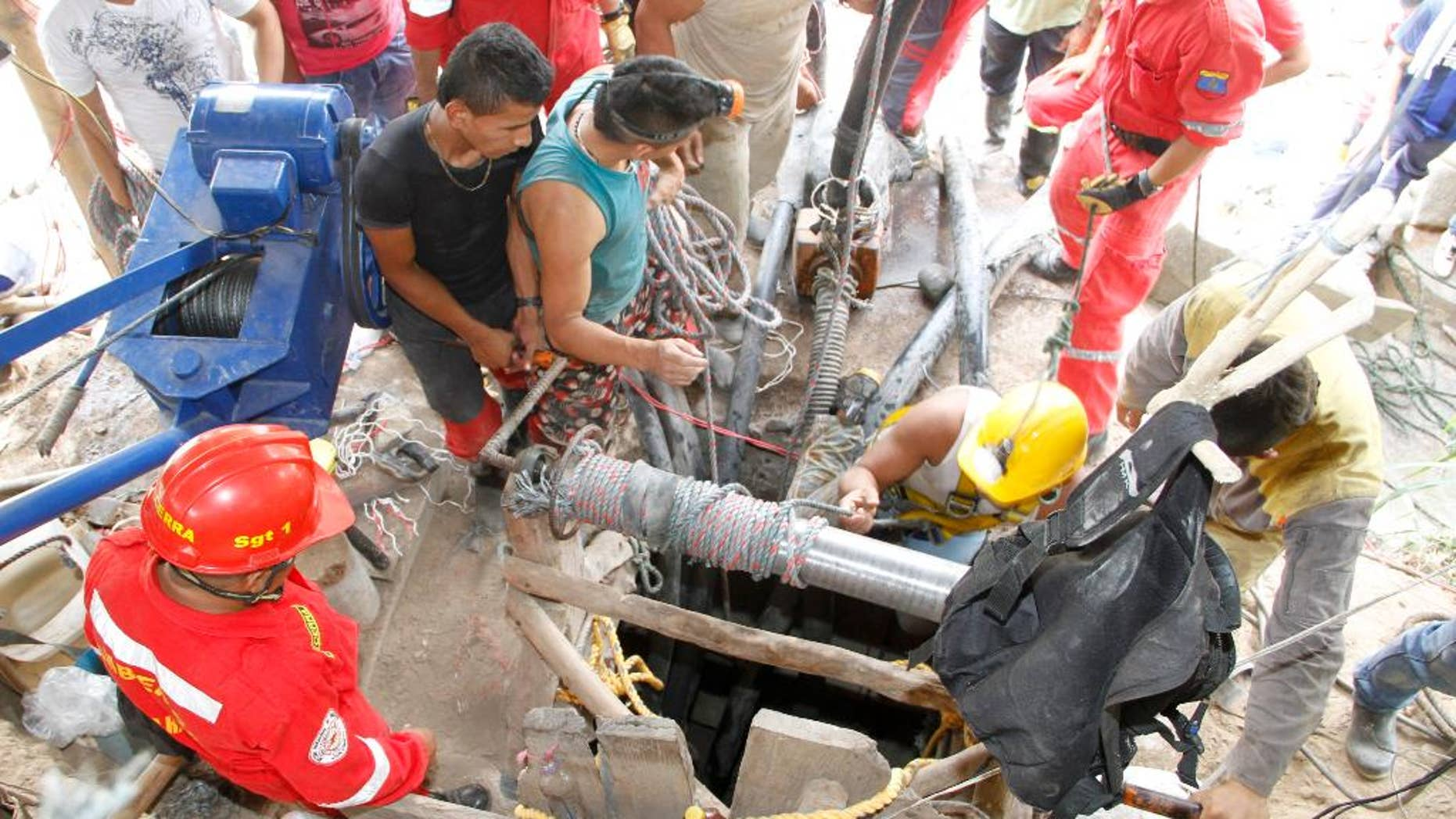 Miners and rescue workers work at the entrance to the El Tunel gold mine in Riosucio, Colombia, Wednesday, May 13, 2015. Fifteen miners are missing and feared dead after water poured into the underground shafts where they were digging early Wednesday. Authorities said the accident was likely triggered by an explosion or power outage that disabled pumps used to extract water and supply oxygen to work crews. (AP Photo/Juan Augusto Cardona)
