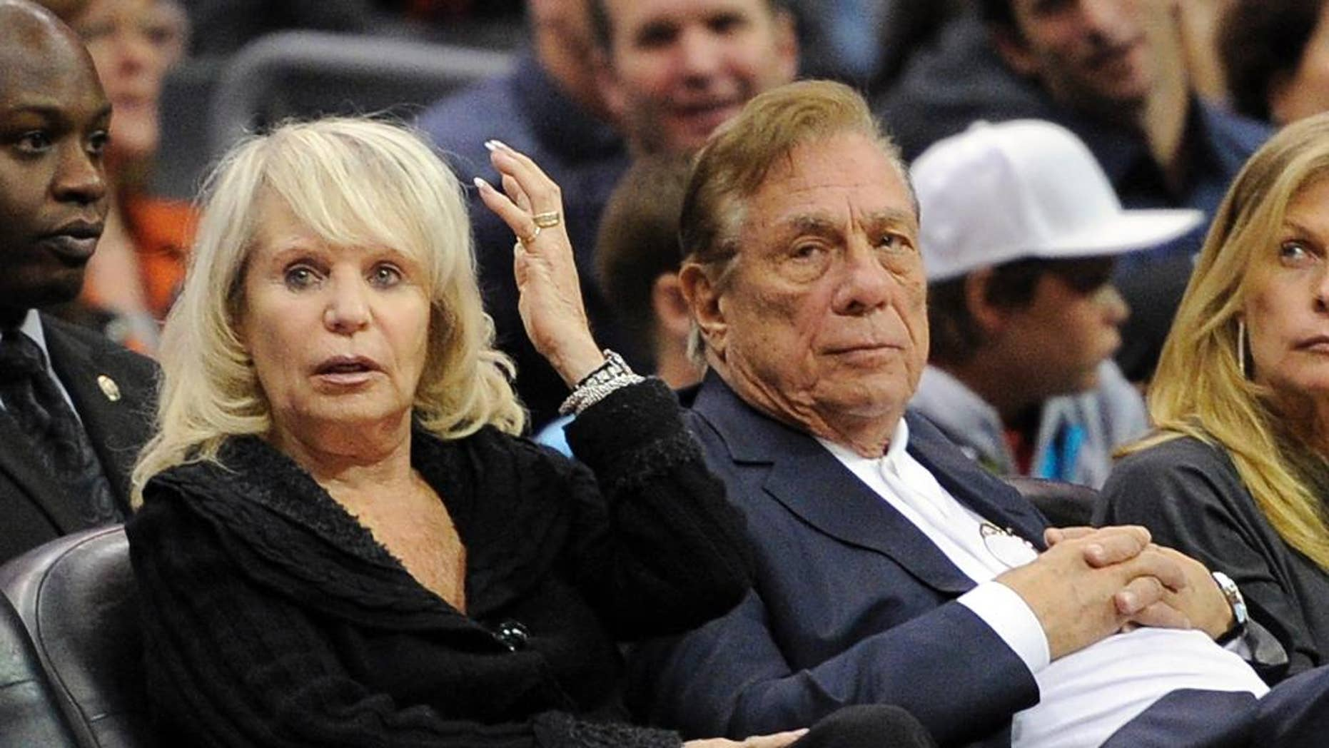 FILE - In this Nov. 12, 2010, file photo, Shelly Sterling sits with her husband, Donald Sterling, right, during the Los Angeles Clippers' NBA basketball game against the Detroit Pistons in Los Angeles. An individual with knowledge of negotiations to sell the Clippers says Shelly Sterling has reached an agreement to sell the team to former Microsoft CEO Steve Ballmer for $2 billion. The individual, who wasn't authorized to speak publicly, told The Associated Press on Thursday, May 29, 2014, that Ballmer and the Sterling Family Trust now have a binding agreement. The deal now must be presented to the NBA. (AP Photo/Mark J. Terrill, File)