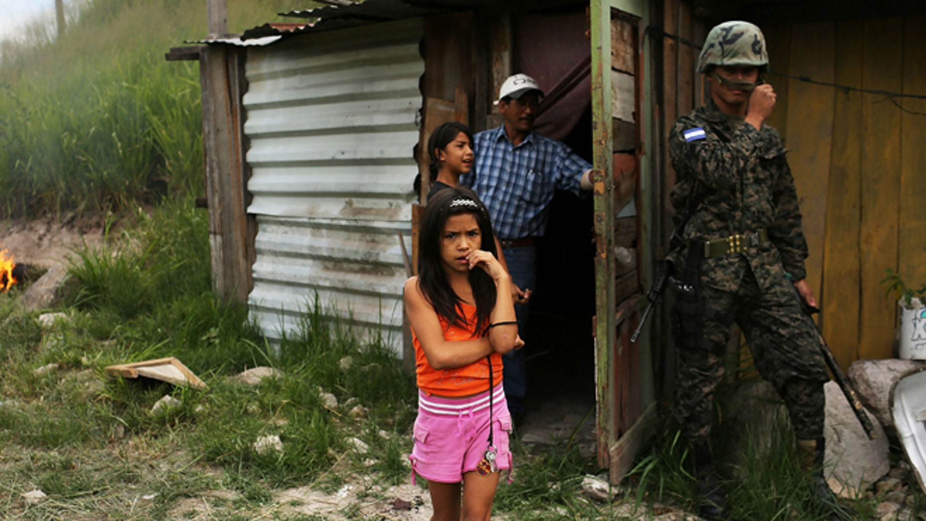 TEGUCIGALPA, HONDURAS - JULY 20:  A young girl and her family stand by their home as police and the army force them and their neighbors to dismantle the shanty town after the government claimed that the settlement was illegal on July 20, 2012 in Tegucigalpa, Honduras. Land disputes are becoming increasingly frequent in Honduras  which is alarming the nation's business class while sowing fears of increased political violence. In a nation where 72% of the poorest landowners hold only 11.6% of cultivated land, tensions are rising as the poor have few places to go and little opportunities for productive employment. Honduras now has the highest per capita murder rate in the world and its capital city, Tegucigalpa, is plagued by violence, poverty, homelessness and sexual assaults. With an estimated 80% of the cocaine entering the United States now being trans-shipped through Honduras, the violence on the streets is a spillover from the ramped rise in narco-trafficking.  (Photo by Spencer Platt/Getty Images)