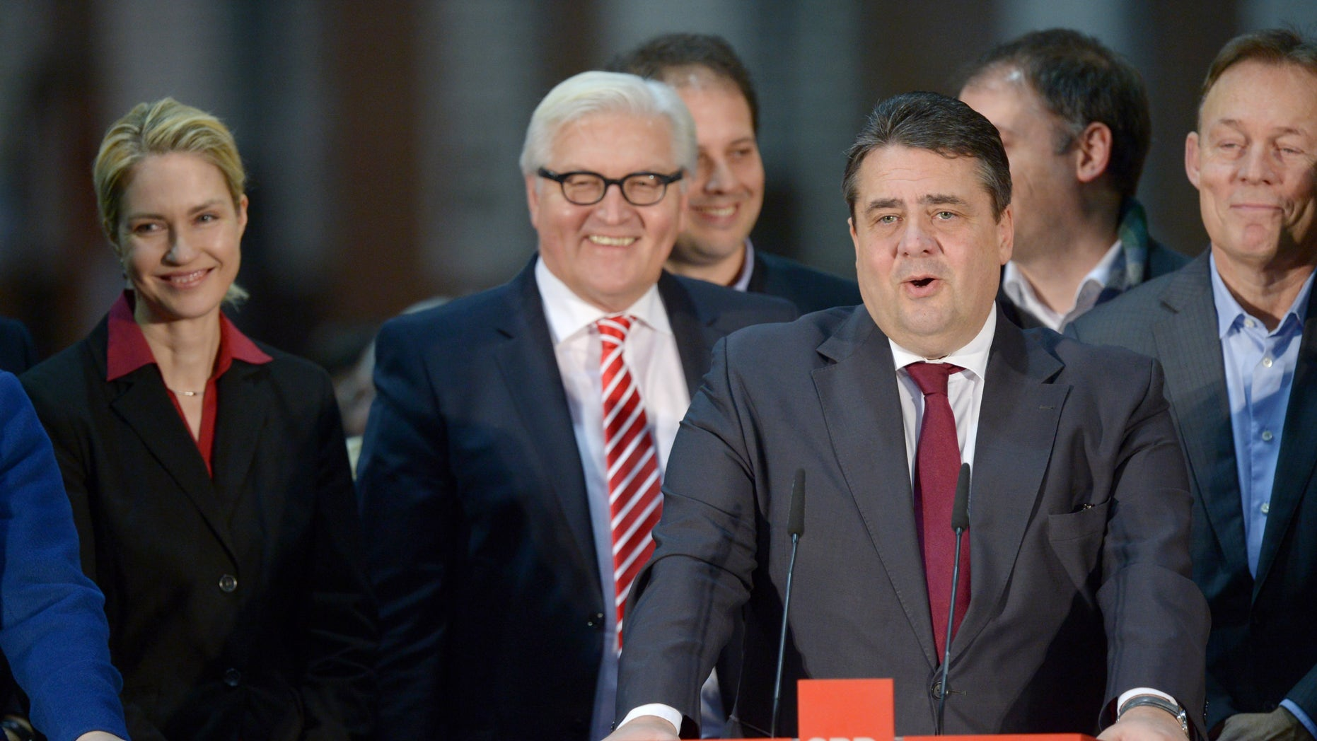 "Chairman of the  Social Democratic Party,SPD,  Sigmar Gabriel, front, a gives a statement  about  the result of the SPD member vote on the coalition agreement with Angela Merkel's  Christian Union Parties'  bloc in Berlin, Germany, Saturday Dec. 14, 2013.  Second left stands former foreign minister Frank-Walter Steimeier., at right Chief Whip Thomas Oppermann, attend.  Germany's main center-left party cleared the way on Saturday for Angela Merkel to start her third term as chancellor, announcing that its members had voted by a large majority to join the conservative leader in government.  Some 76 percent of members who took part approved a deal to form a ""grand coalition"" government of right and left under Merkel and about 24 percent voted against. (AP Photo/dpa, Rainer Jensen)"