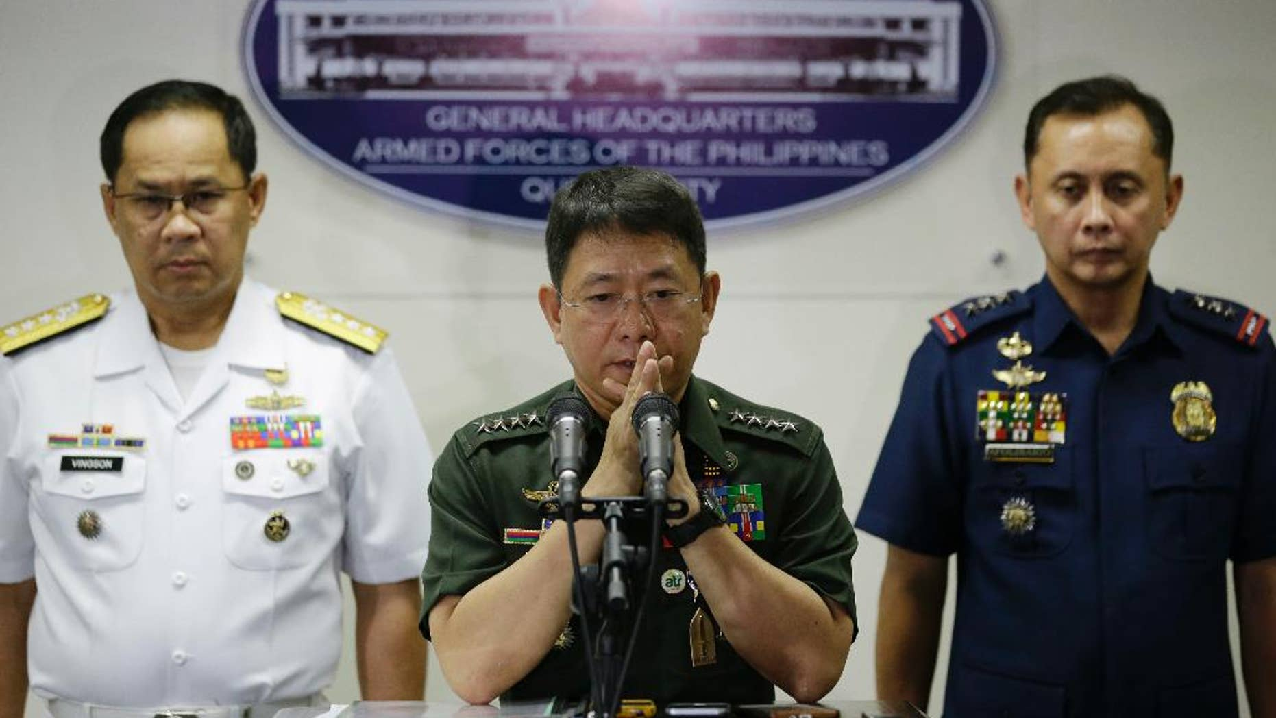 Philippine military chief of staff Gen. Eduardo Ano, center, gestures beside Philippine Navy Vice Adm. Narciso Vingson, left, and Philippine National Police Deputy Director for Administration Ramon Apolinario during a press conference at Camp Aguinaldo, the military headquarters in Quezon city, north of Manila, Philippines, Wednesday, April 12, 2017. Philippine troops battling militants in a central province killed a key Abu Sayyaf commander who had been blamed for the beheadings of two Canadians and a German hostage and was apparently attempting another kidnapping mission, Ano said Wednesday. (AP Photo/Aaron Favila)