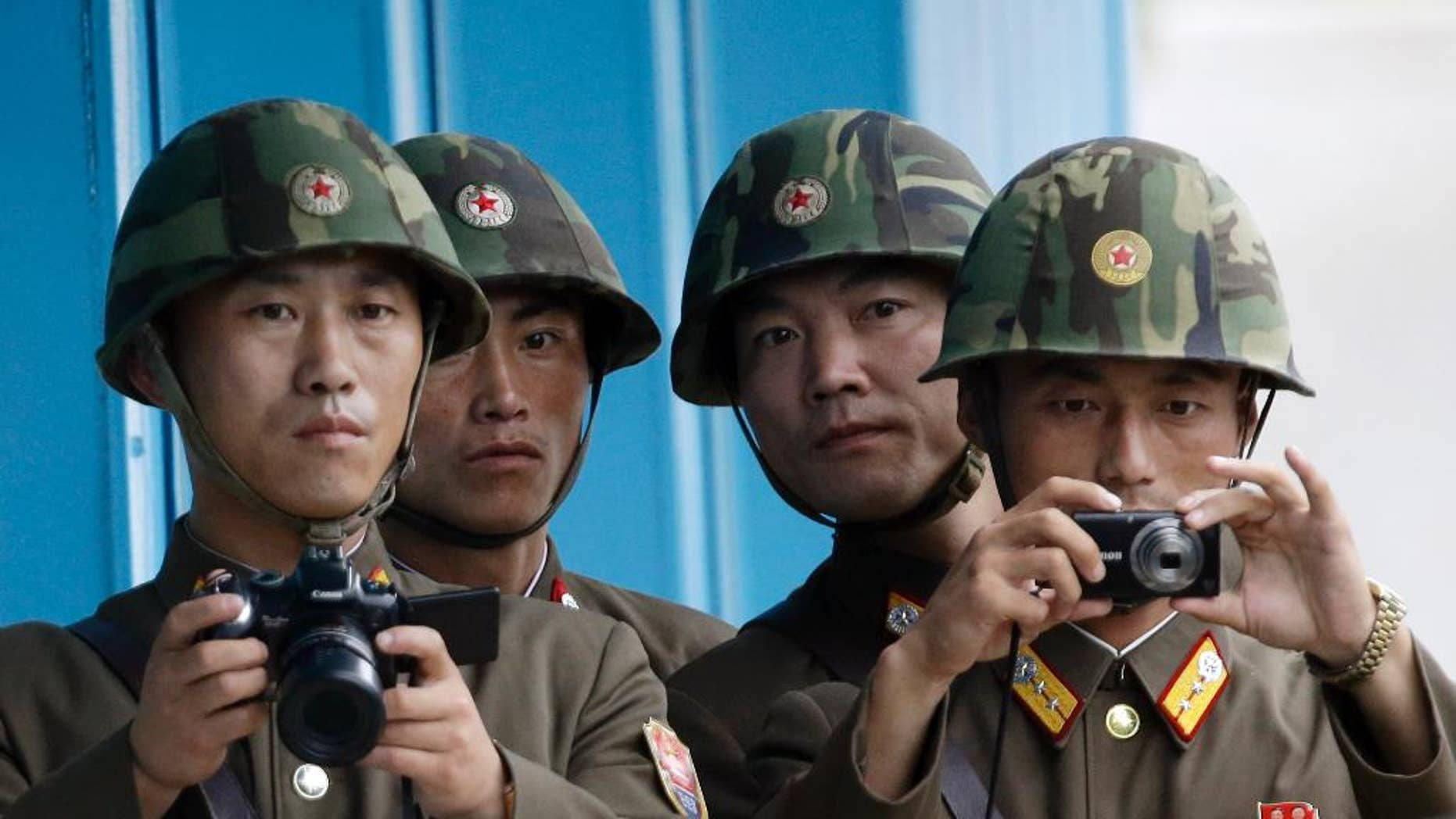 In this Saturday, July 27, 2013 photo, North Korean soldiers watch the south side with cameras at the border village of Panmunjom, which has separated the two Koreas since the Korean War, in Paju, north of Seoul, South Korea. Seoul defense officials said South Korean troops have fired warning shots after North Korean soldiers approached too close to the border separating the rival countries. (AP Photo/Lee Jin-man)