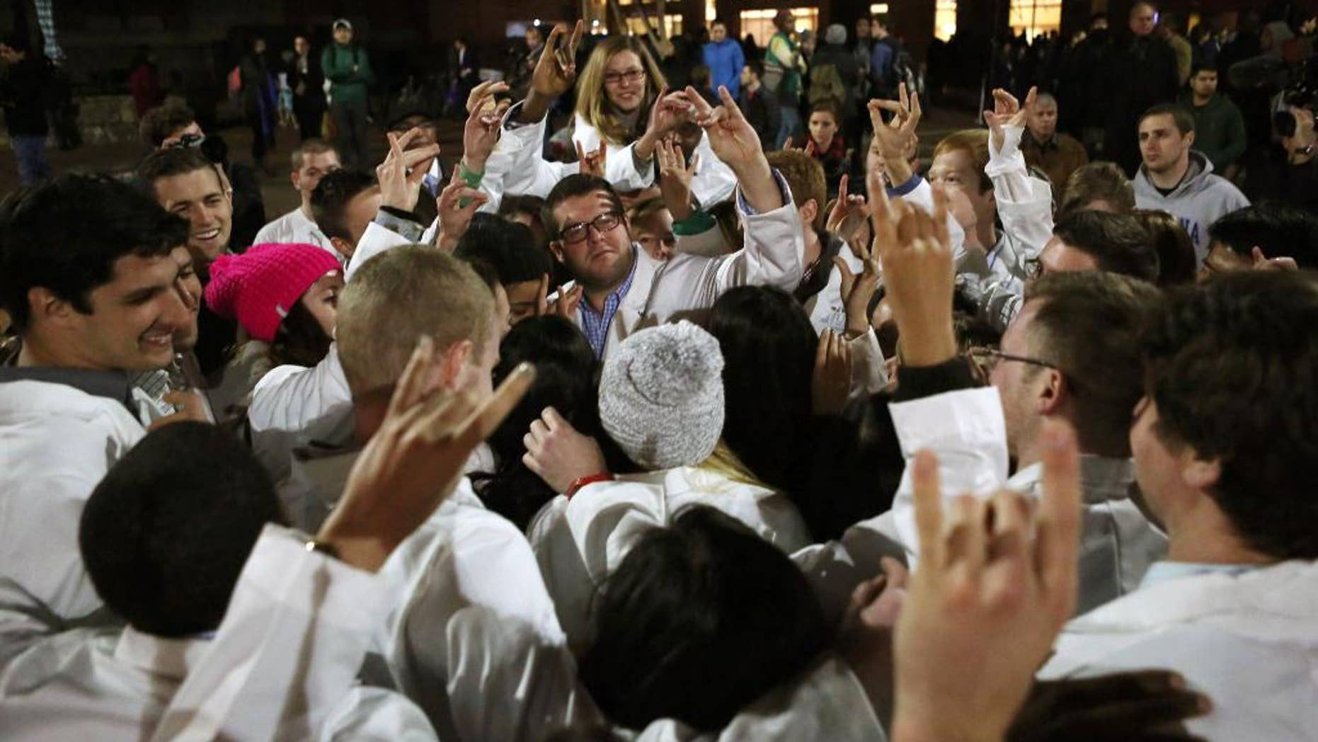 UNC Dental School students make the North Carolina State University Wolfpack sign following a candlelight vigil for their slain classmate, who, along with two others, was killed at a condominium near UNC-Chapel Hill, Wednesday, Feb. 11, 2015, in Chapel Hill, N.C. Craig Stephen Hicks appeared in court on charges of first-degree murder in the Tuesday deaths of Deah Shaddy Barakat, his wife Yusor Mohammad and her sister Razan Mohammad Abu-Salha. (AP Photo/The News & Observer, Al Drago)