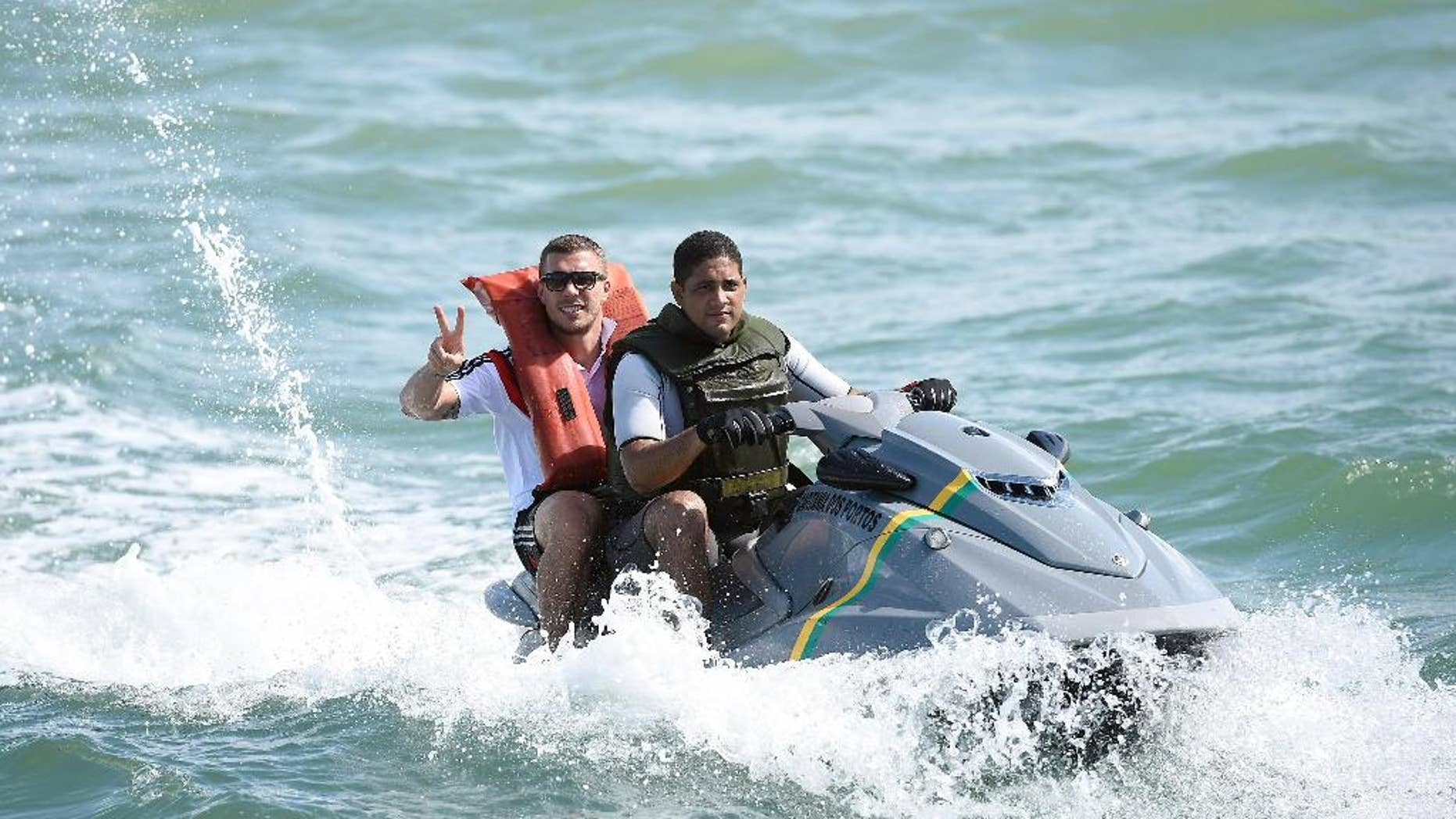 German national soccer player Lukas Podolski poses on a jet ski in Santo Andre near Porto Seguro, Brazil, Tuesday, June 10, 2014. The German team got some motivation help from explorer and adventurer Mike Horn during a sailing outing near their camp on Brazil's Atlantic coast. (AP Photo/Markus Gilliar, pool)