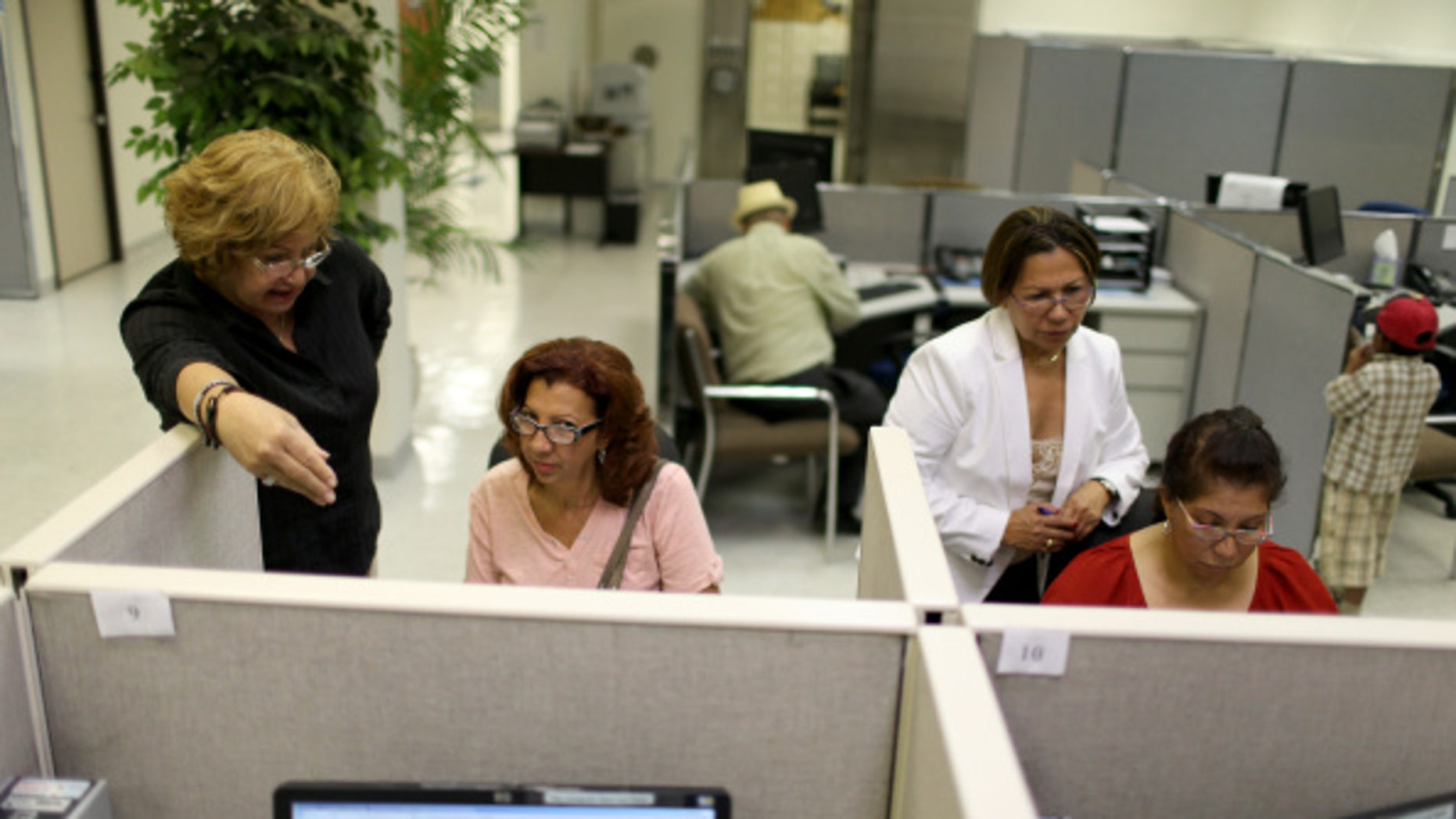 MIAMI, FL - AUGUST 01: Raisa Alvarez (L) helps Ana Celeste Reynoso as Maria Tutiven (2nd R) helps Idali Valasquez as they look for job opportunities on the computers at CareerSource Florida on August 1, 2014 in Miami, Florida. The Labor Department announced that U.S. employers added 209,000 new jobs in July and that the unemployment rate edged up to 6.2 percent as more workers joined the labor force.  (Photo by Joe Raedle/Getty Images)