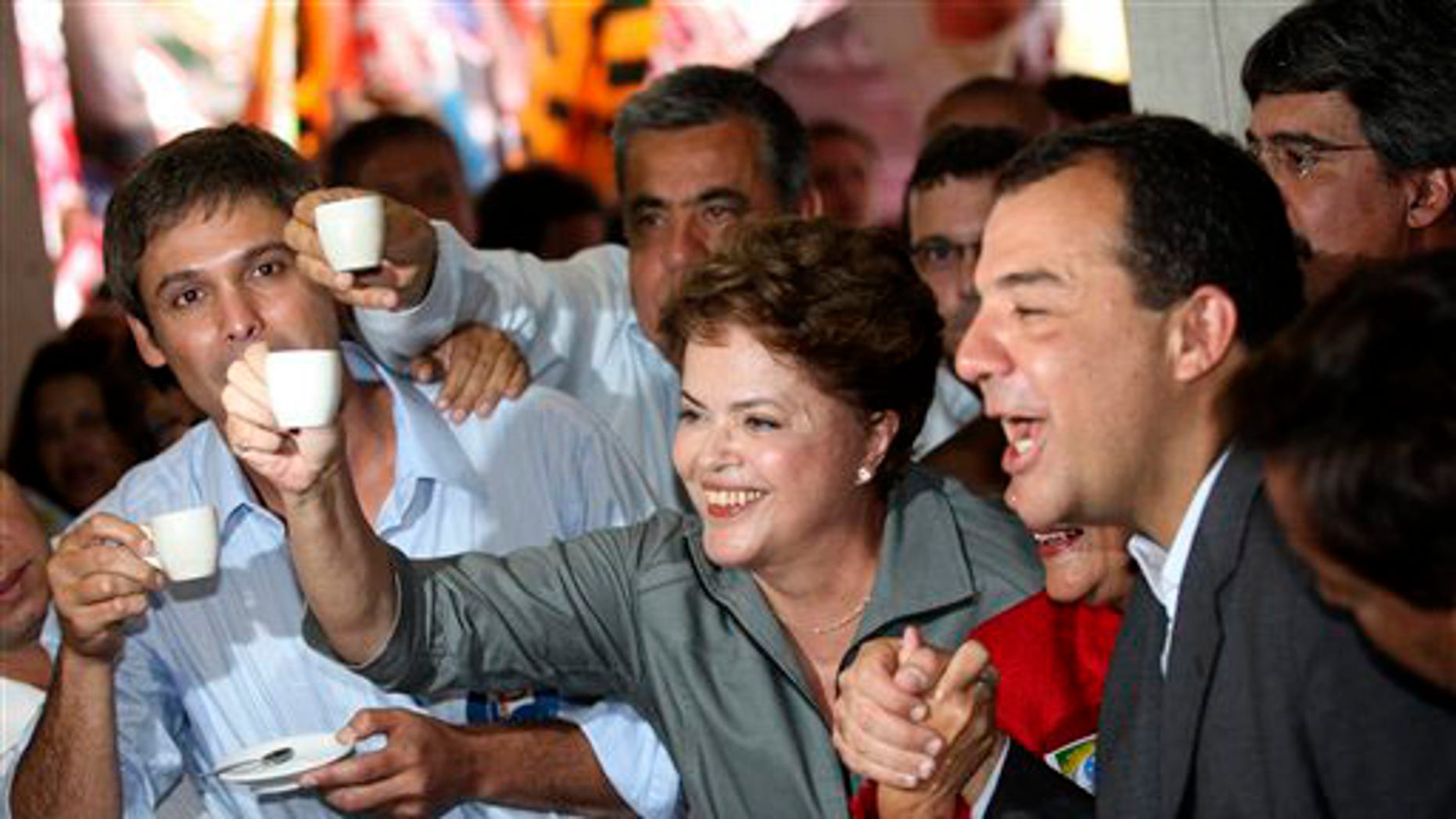 Brazil's Workers party presidential candidate Dilma Rousseff, center, holds up a cup of coffee at a coffee shop during a campaign rally in Rio de Janeiro, Brazil, Monday, Sept. 20, 2010.