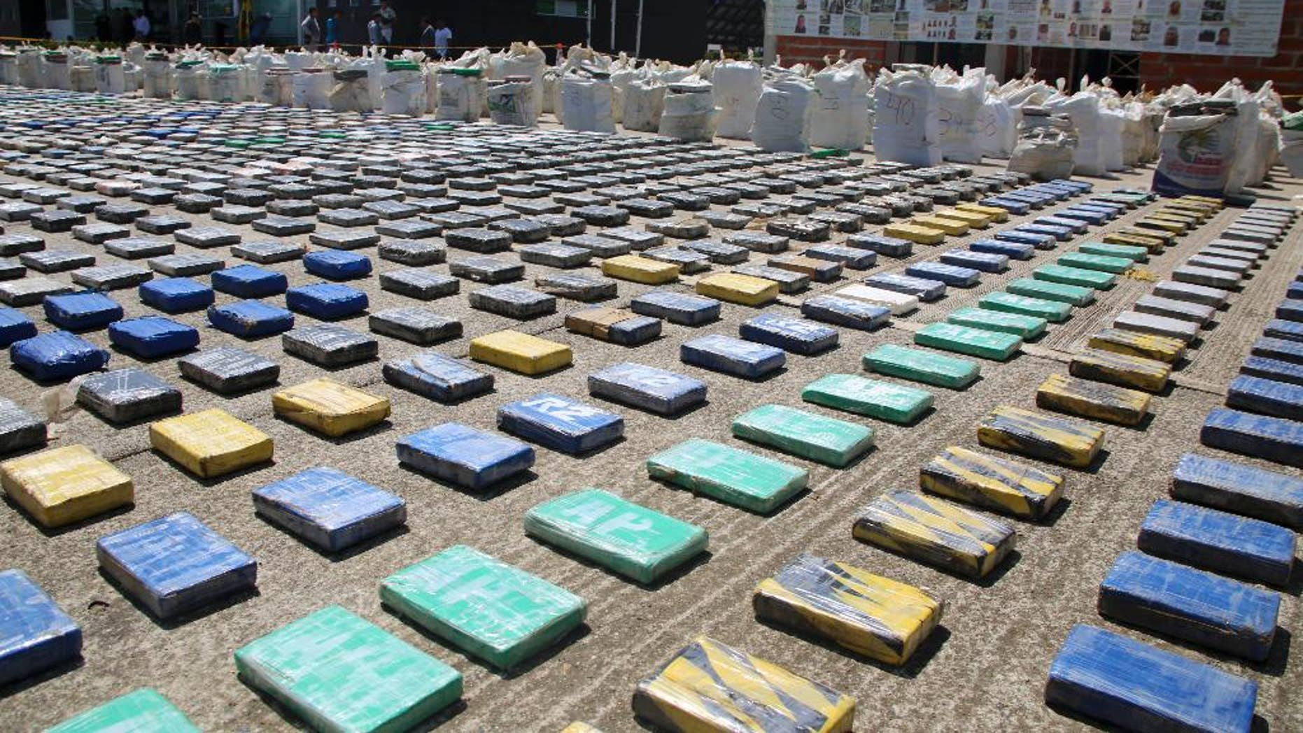 This photo released by Colombia's National Police shows packages of cocaine on display in Necocli, in the northwestern state of Antioquia, Colombia, Sunday, May 15, 2016. The National Police agency said commandos backed by helicopters seized about eight tons of cocaine on a banana plantation belonging to a gang known as the Clan Usuaga and was apparently destined for the Caribbean and then to the United States. Authorities say its the biggest cocaine seizure in Colombia's history. (Colombia National Police via AP)